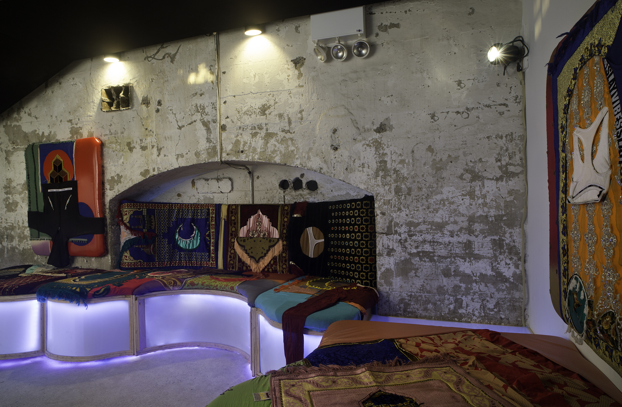 Custom lounge unit with eight unique seating panels made from pleather, artist's underwear, and mass produced prayer rugs lined with LED lighting