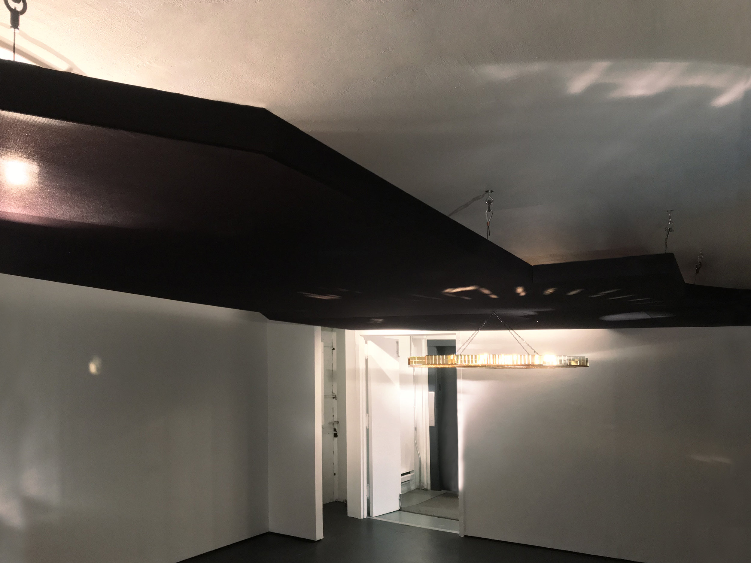 [Feat. ], On Whiteness , at The Kitchen, a lowered ceiling made from acoustic speaker fabric and wood framing - a black and gold plexiglass chandelier that spins on a disco-motor, 2018