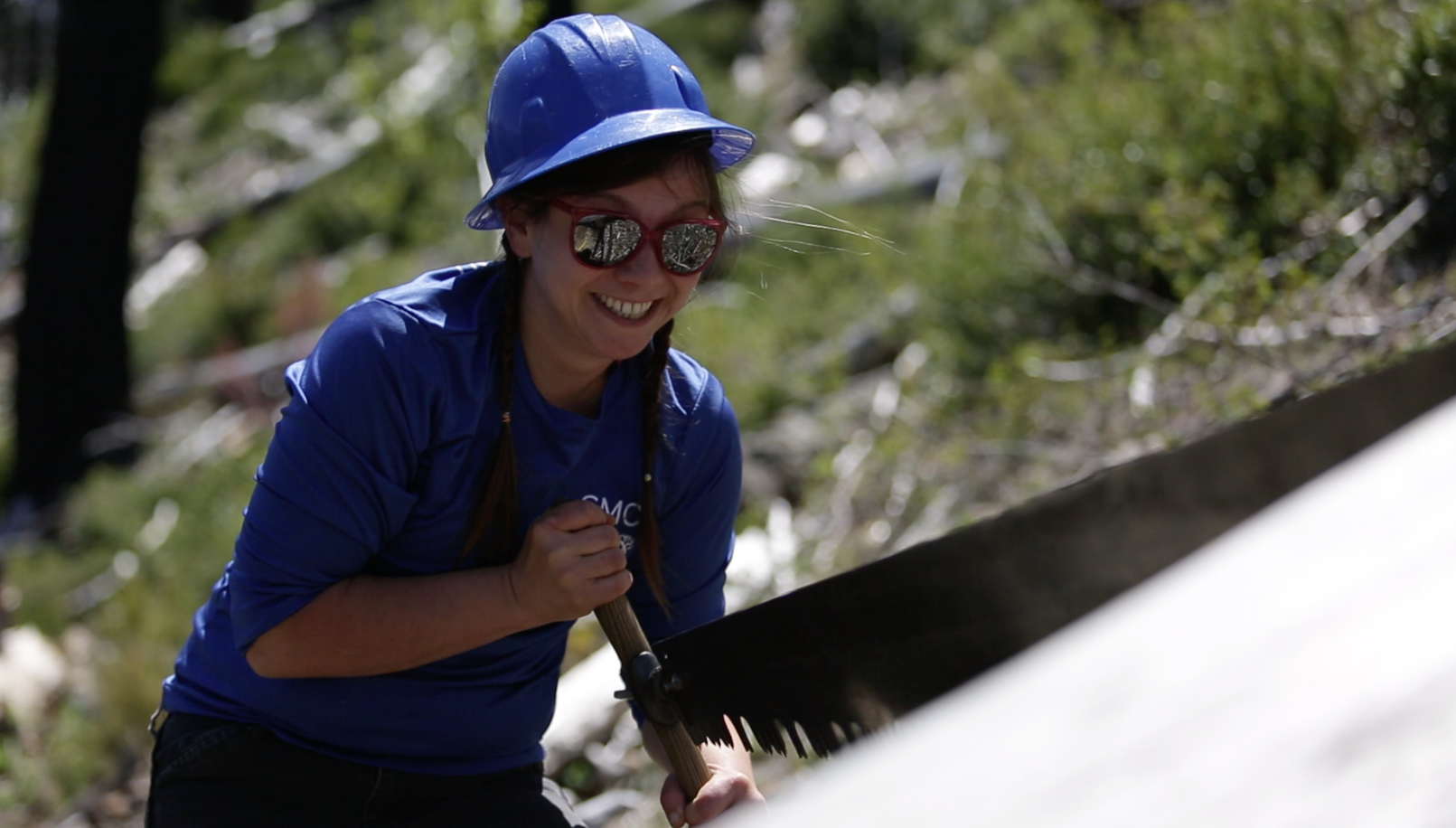 Jill Stokes takes her turn on a crosscut saw.