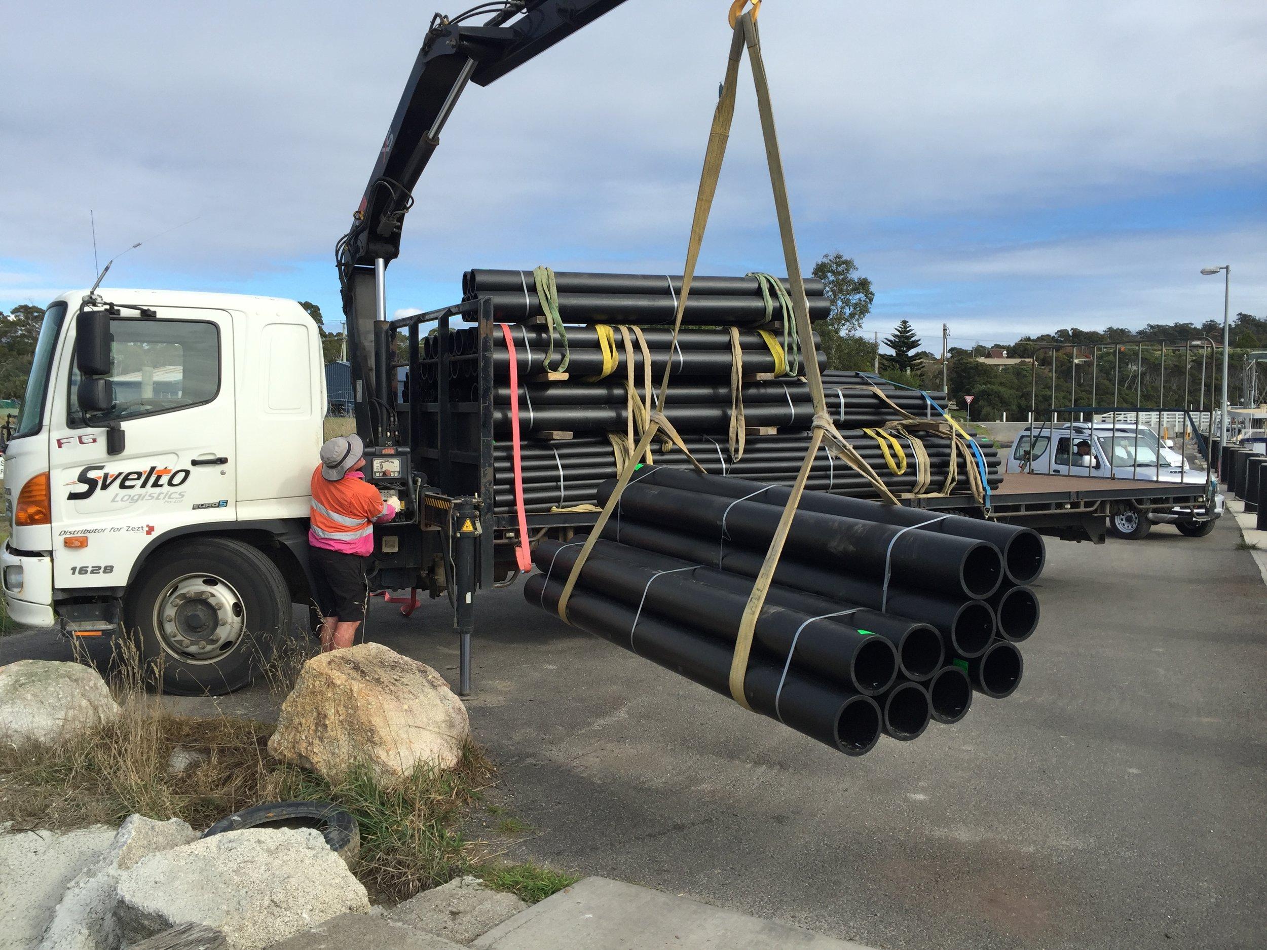 Unloading piping on dock Bridport, Tasmania.