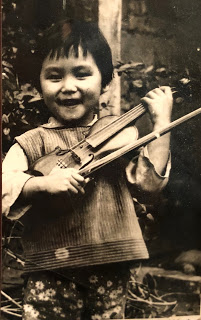 Jessica at 3 years old holding her first violin which her father made for her