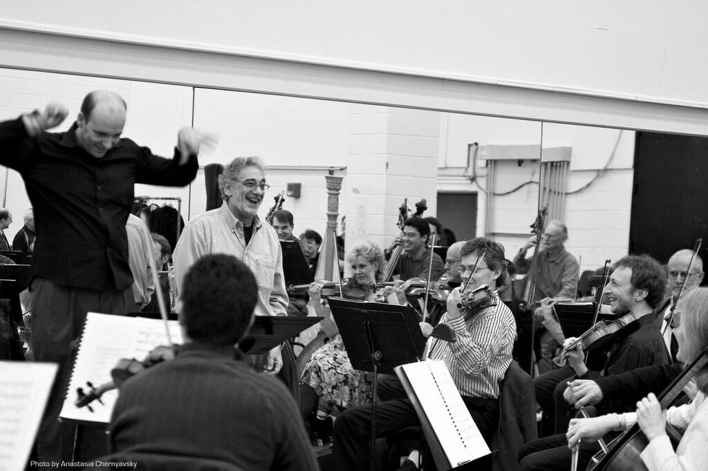 Domingo and conductor Emmanuel Villaume share a light moment with the orchestra .  Photo Credit: Anastasia Chernyavsky