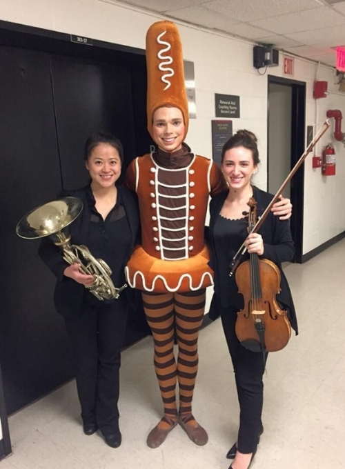 """Second hornist Wei-Ping Chou and principal violist Ally Goodman pose with a Gingerbread Man from ABT's production of """"Whipped Cream"""""""