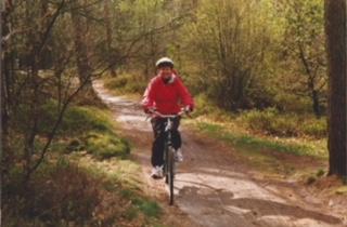 Photo of Meg biking in the forest -- Netherlands