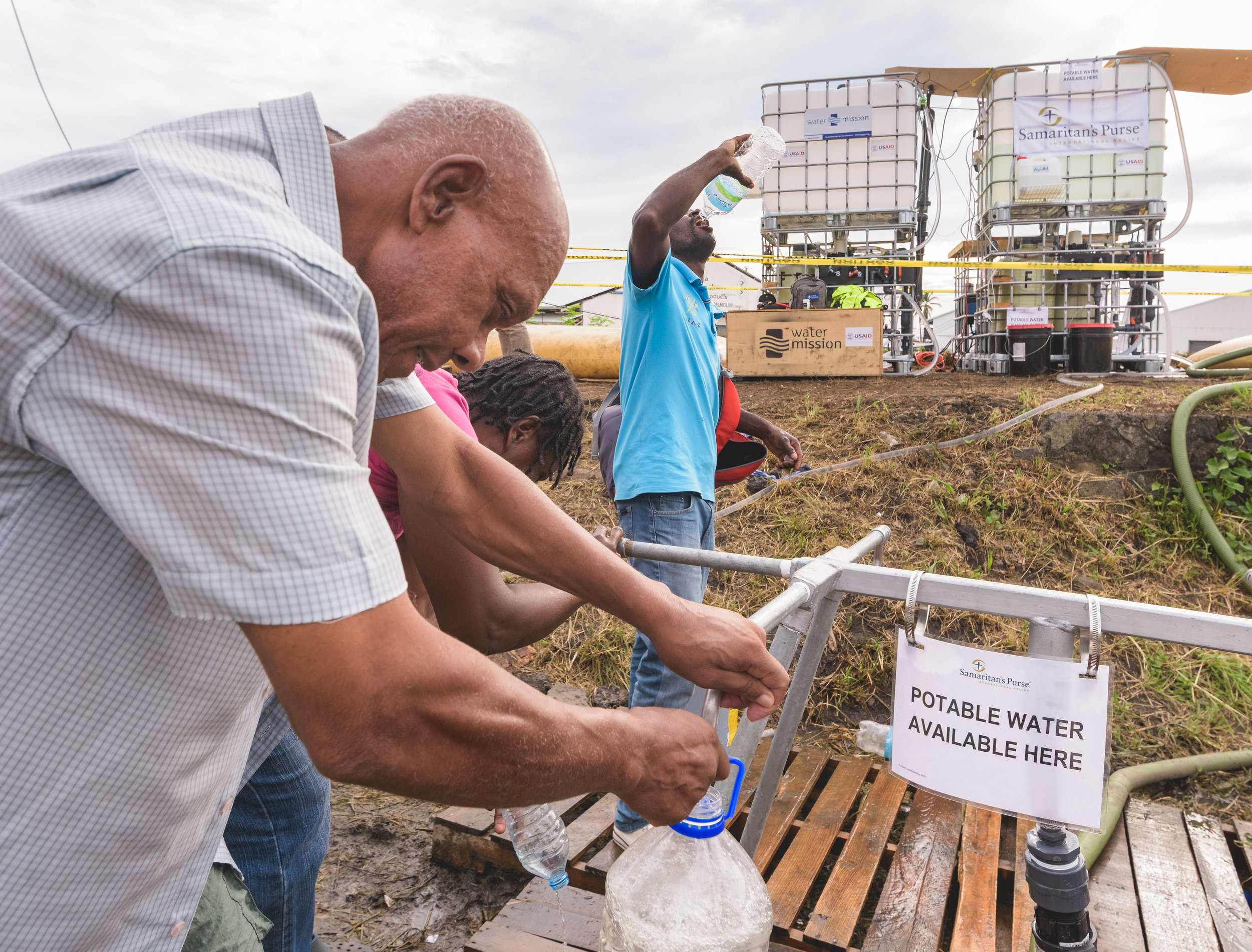 Roseau, Dominica - A Dominican man drinks fresh water, while another fills his bottle at a water distribution station. The whole island was left without power and water for weeks.