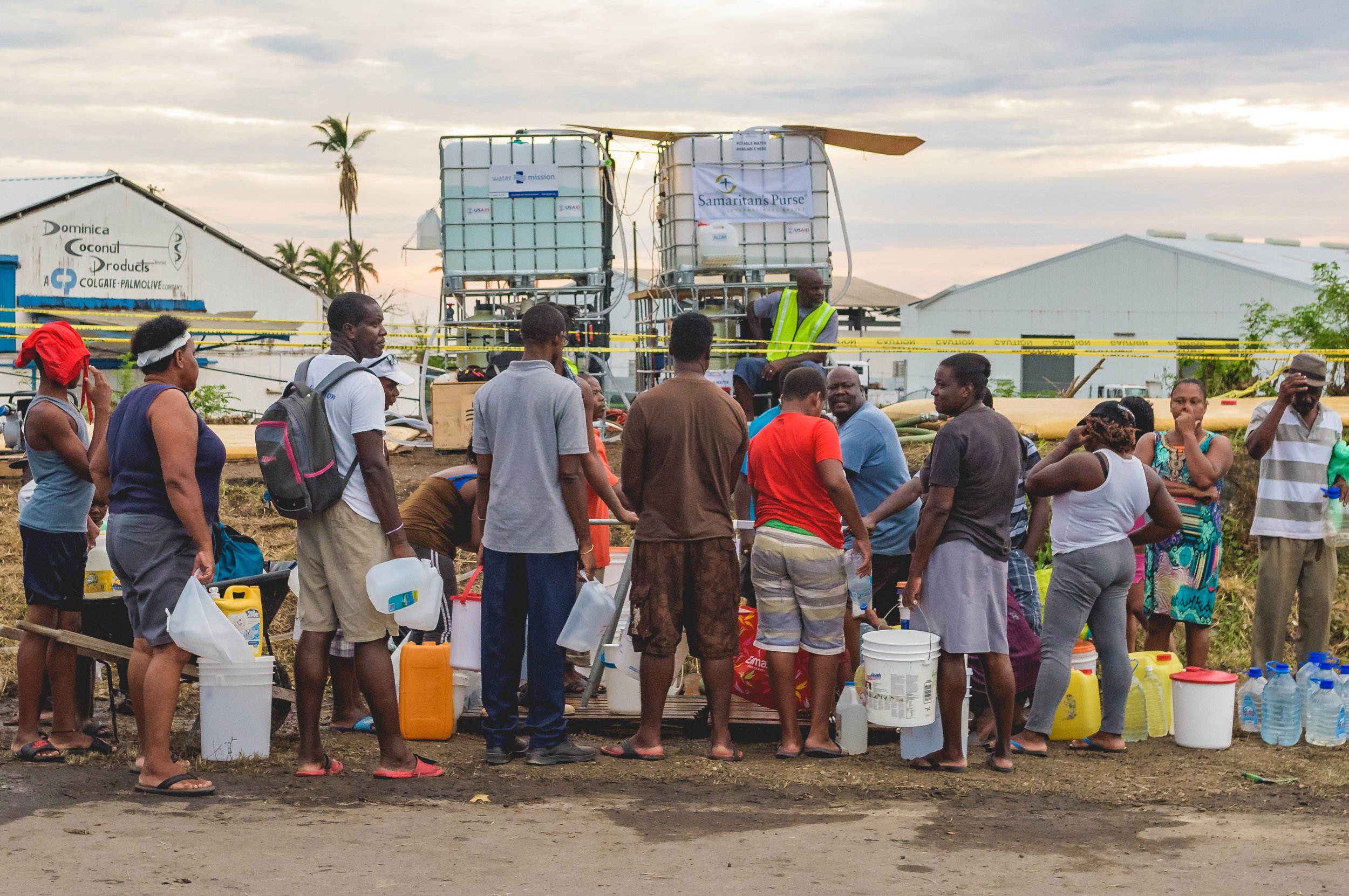 Roseau, Dominica - Residents line up at a water distribution station with anything that will carry water.