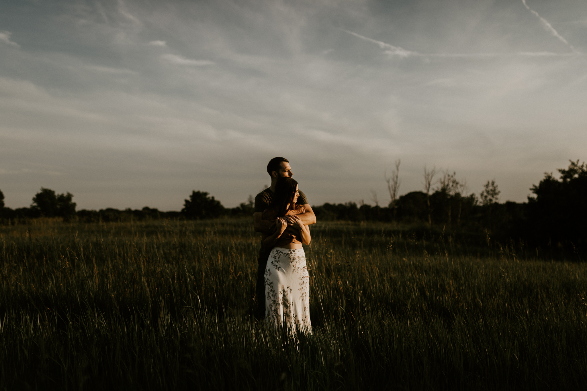 Couple standing, looking out at the sunset in Howell, Michigan