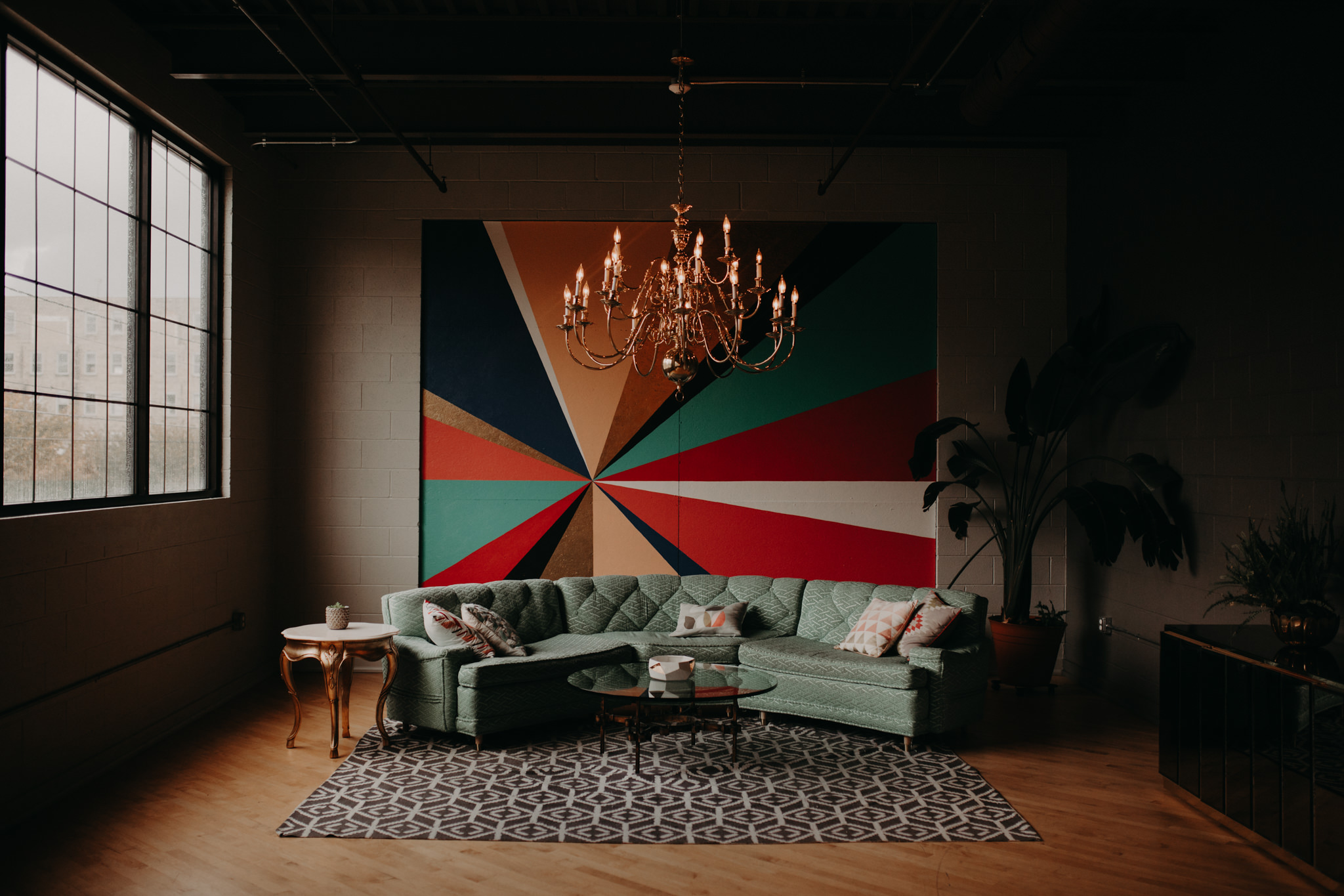 Rainbow mural with a blue couch and chandelier