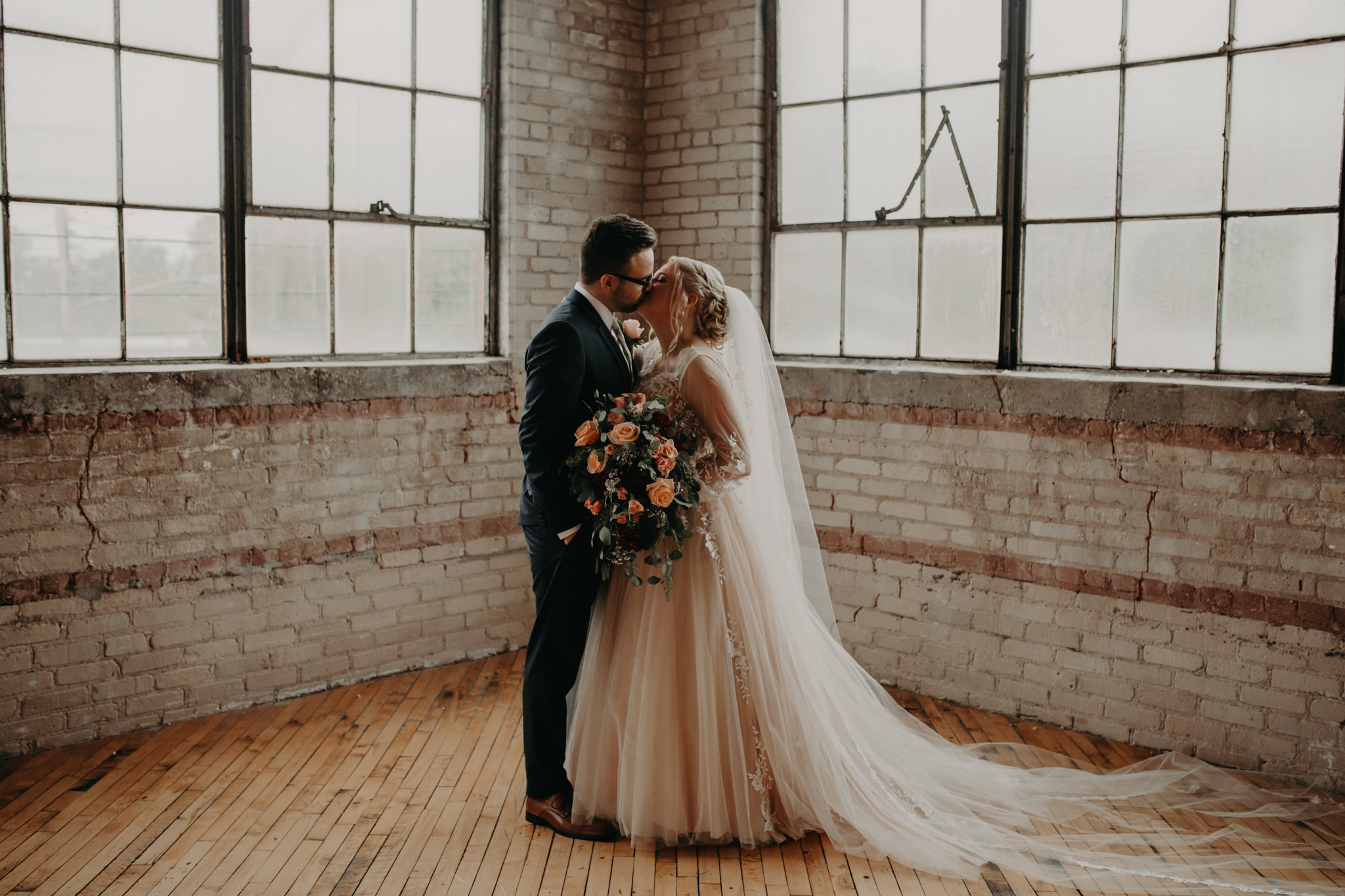 Bride and groom kissing in front of square windows and brick