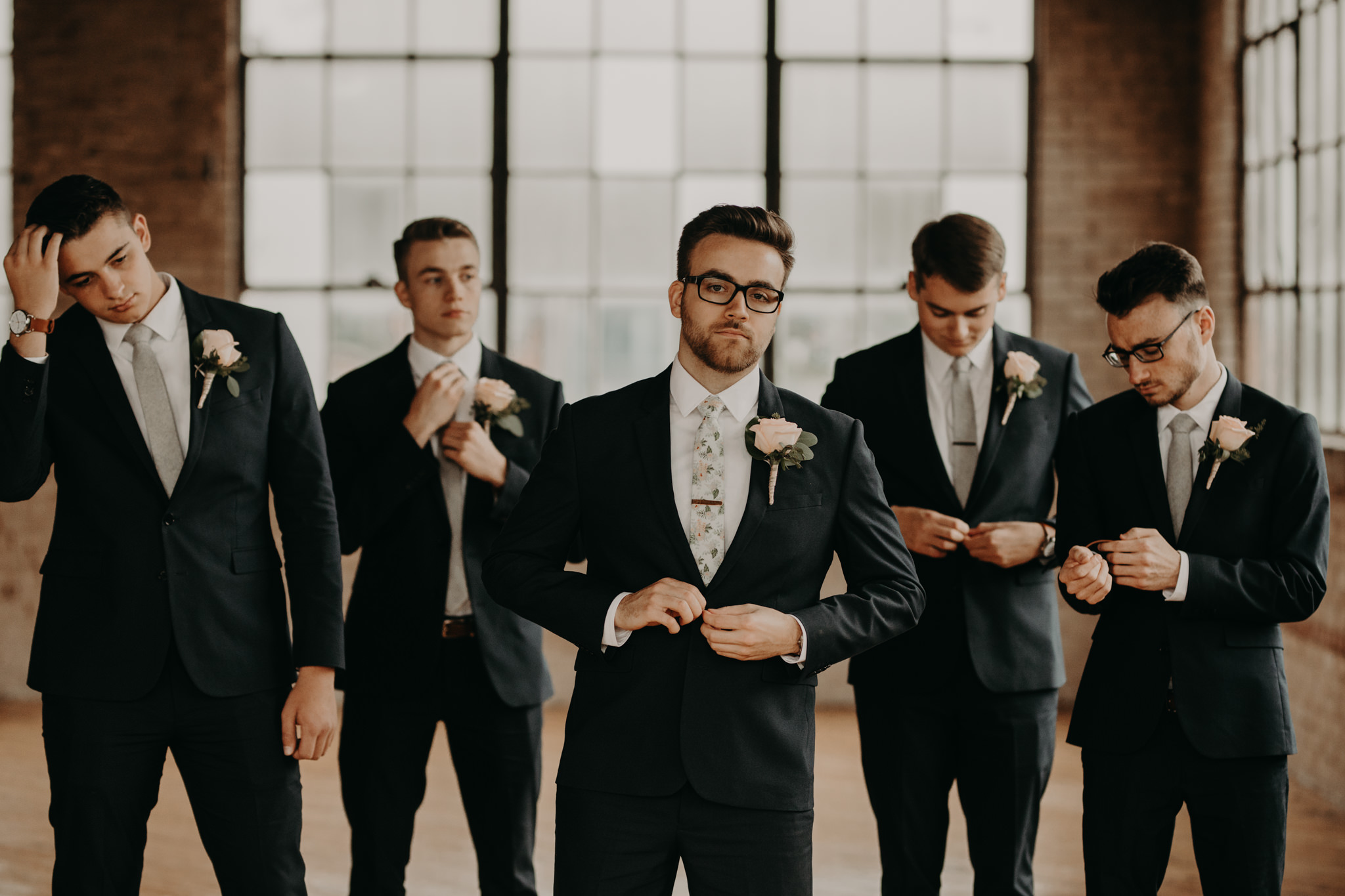 Groomsmen in navy suits and floral ties standing in front of windows and brick