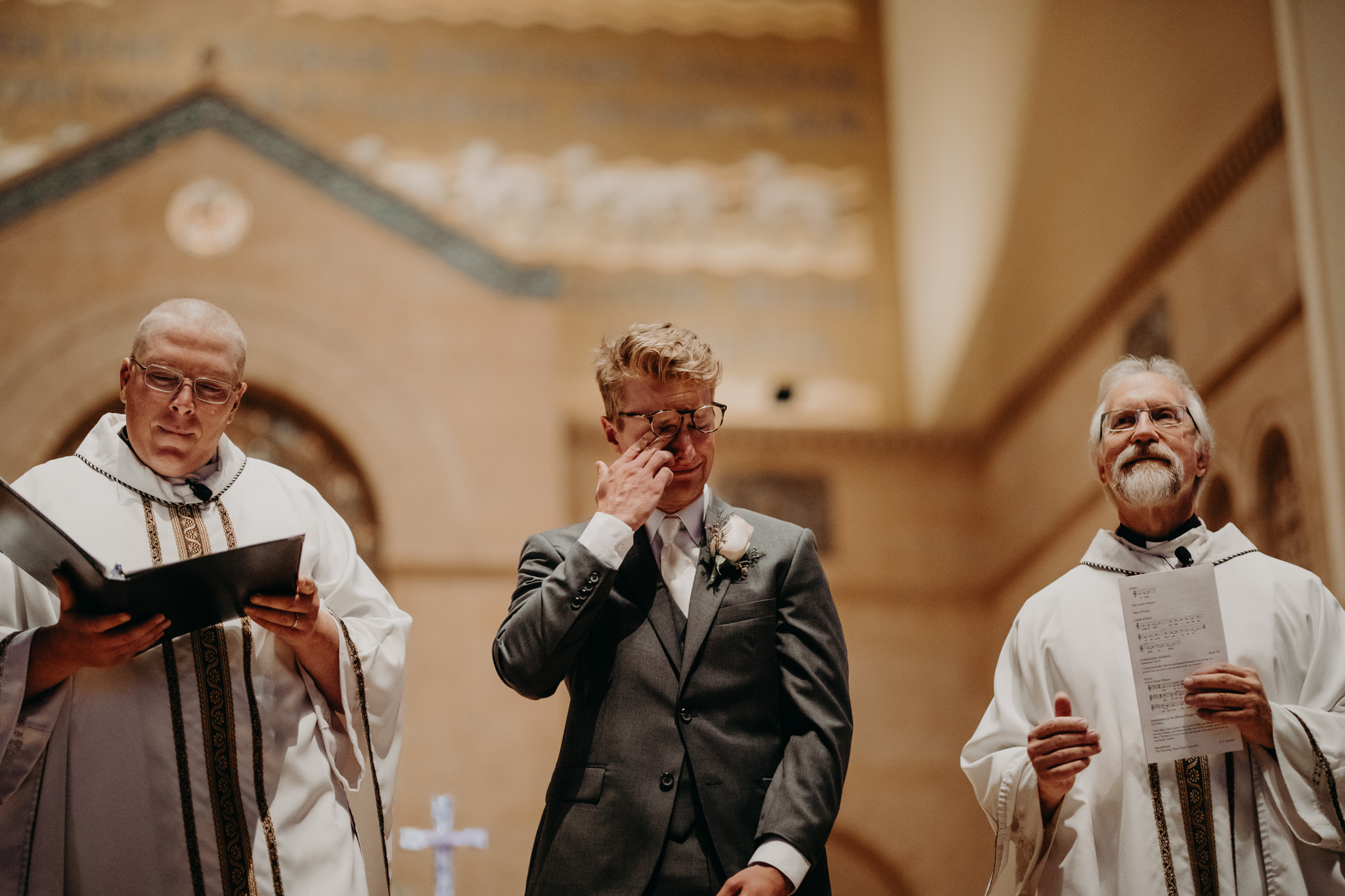 Groom crying at St. Peter Cathedral in Marquette