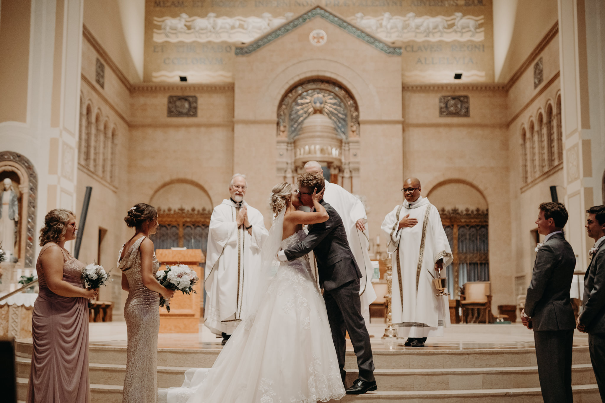 Bride and groom's first kiss at St. Peter Cathedral in Marquette