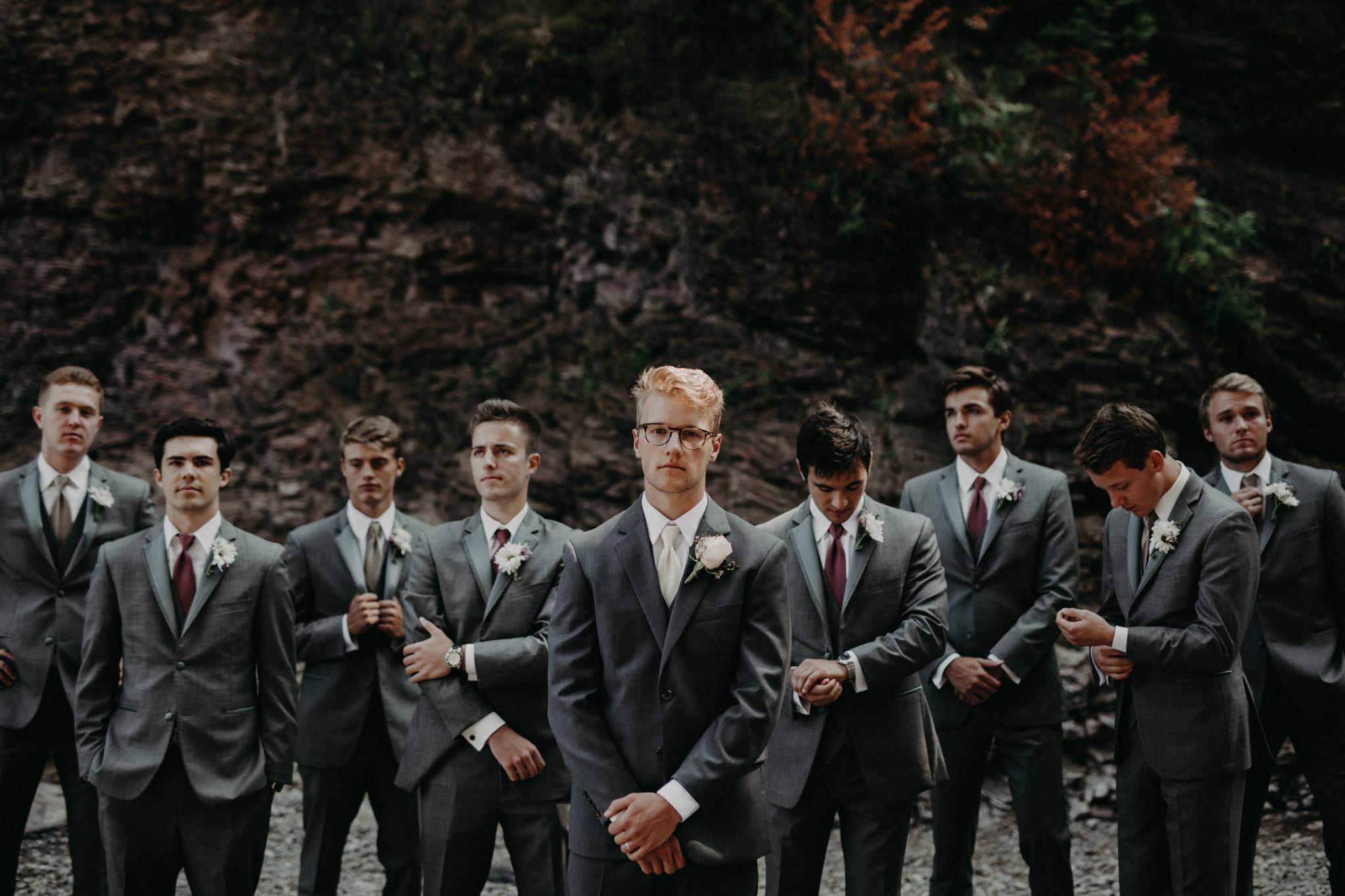 Groomsmen standing in front of black rocks