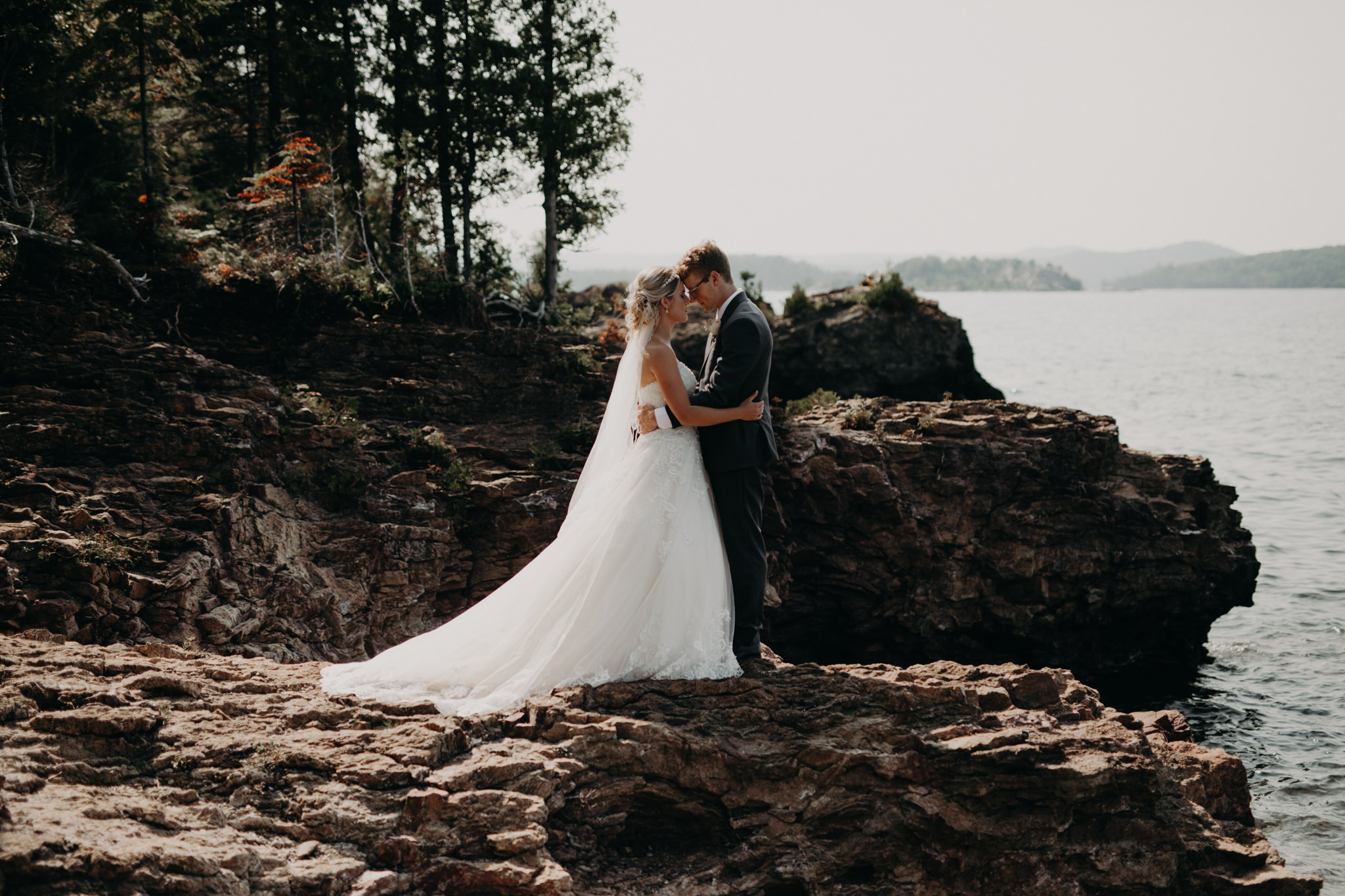 Bride and groom on black rocks in Marquette