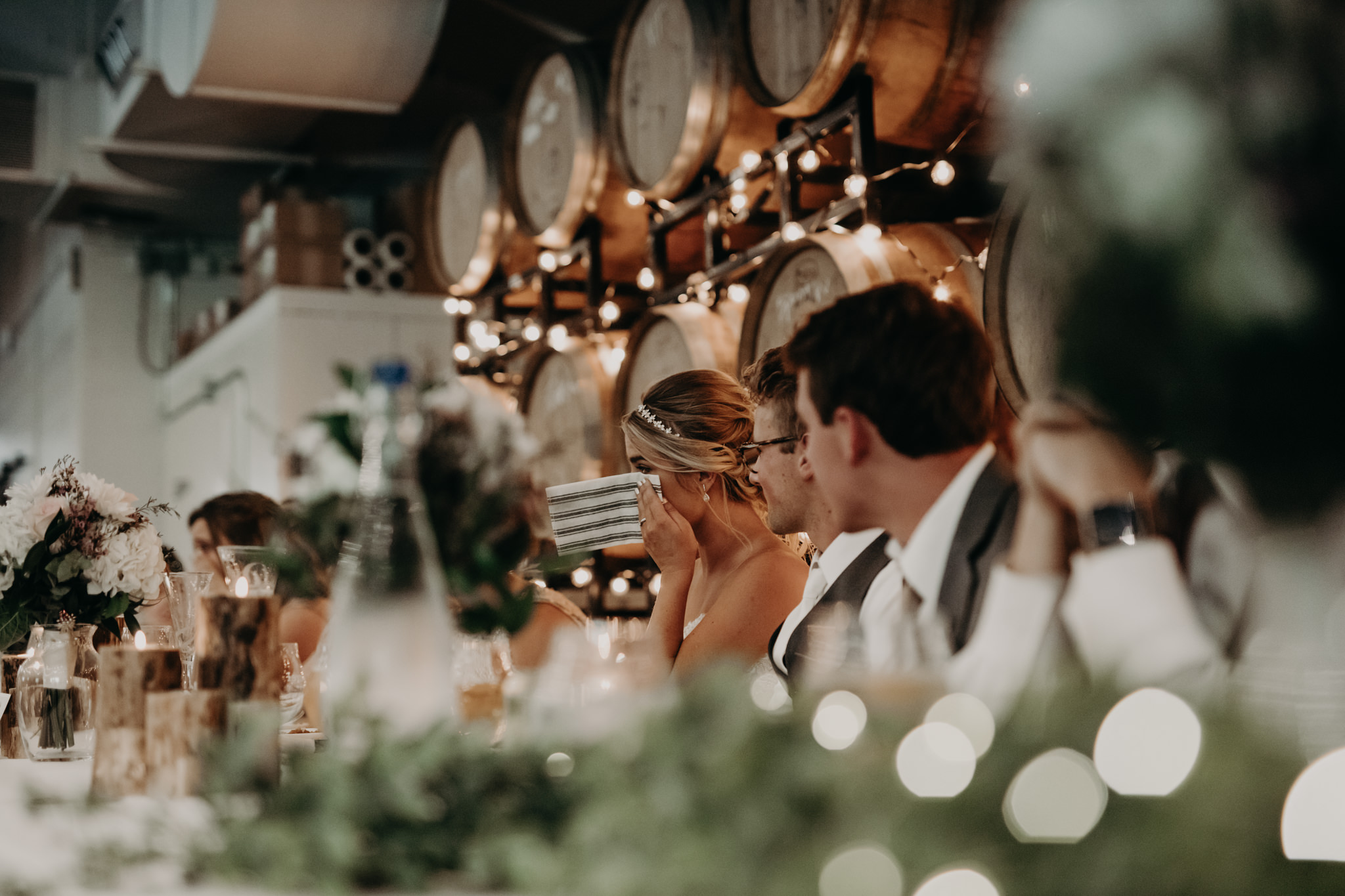 Bridal party at head table with whiskey barrels behind them