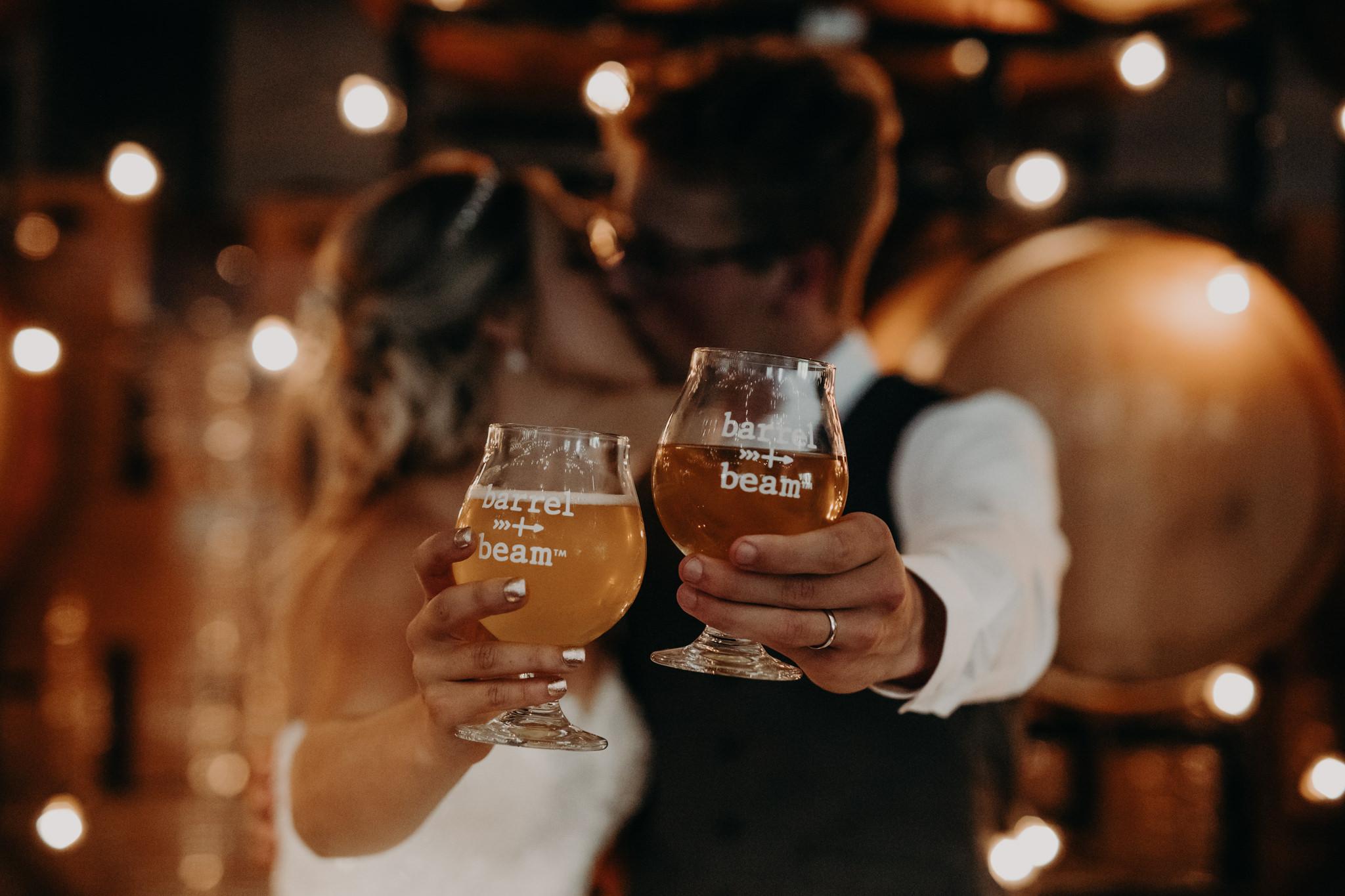 Bride and groom holding Barrel + Beam beer glasses