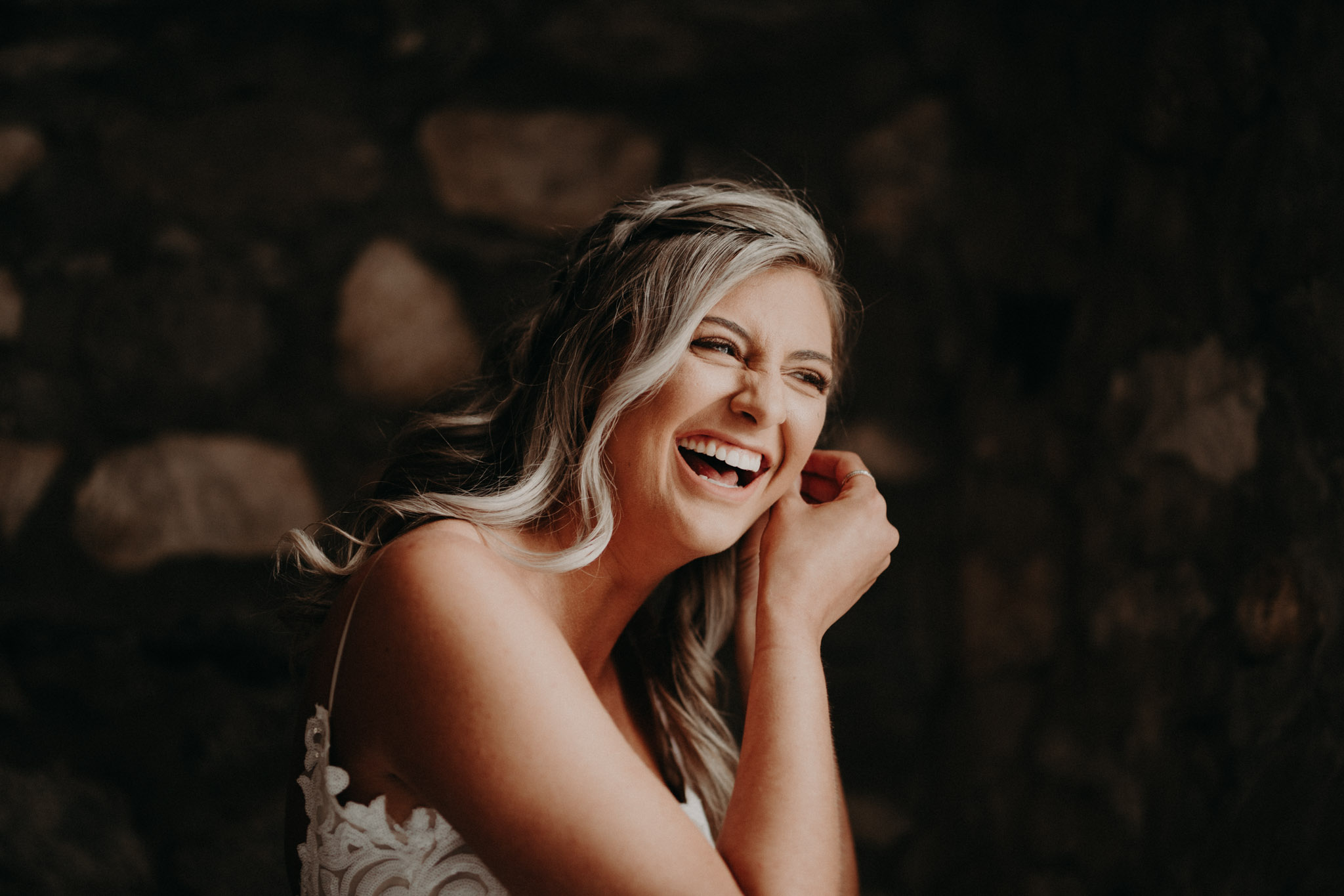 Bride laughing while putting earrings on