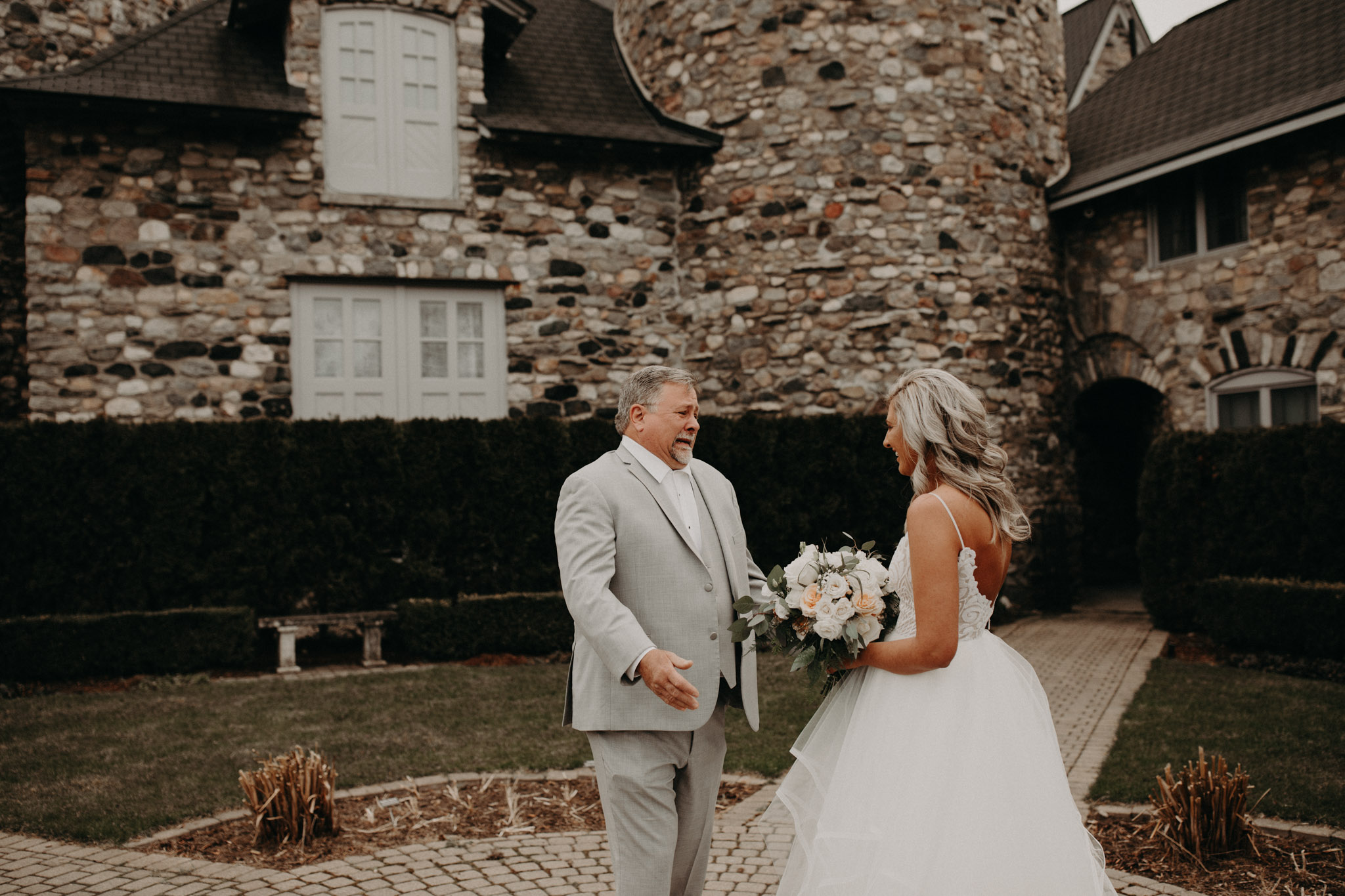 Bride and Dad first look in front of stone wall at Castle Farms