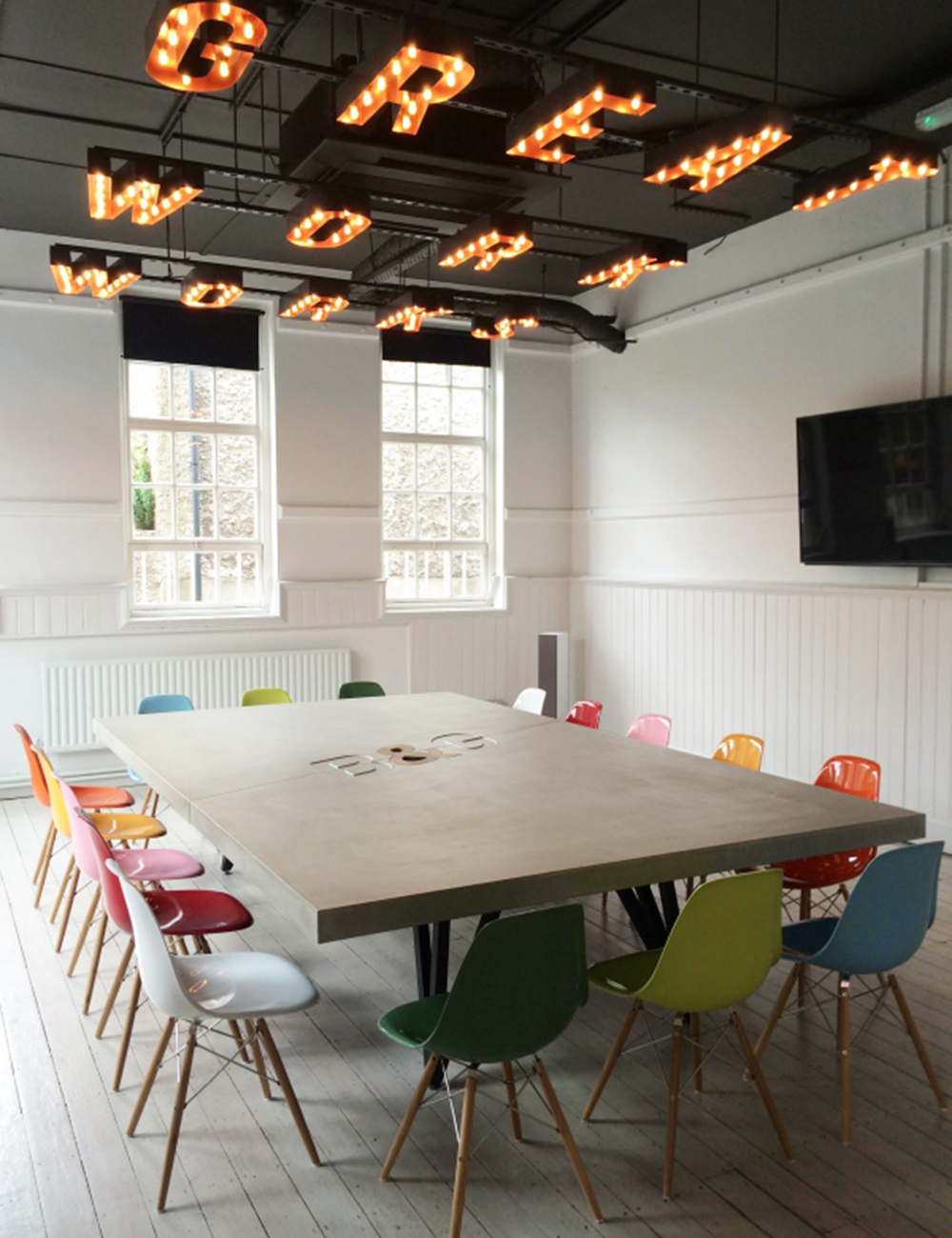 Boys & Girls  creative agency use our colourful Eames-style DSW chairs in their busy boardroom.
