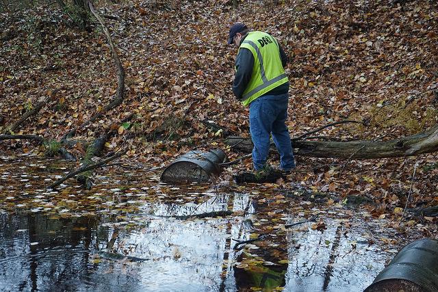 DEQ geologist investigates steel drums for potential PFAS contamination. Photo Credit: Michigan DEQ