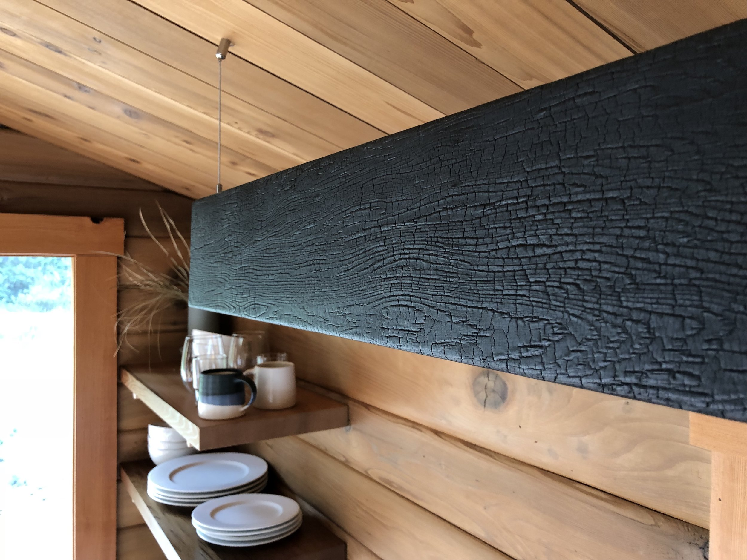 Shou Sugi Ban - DETAILS: BRINGING THE OUTDOORS IN, I CREATED LED LIGHTING WITH THE SAME CHARRED CEDAR THAT CLADS THE EXTERIOR WALLS.
