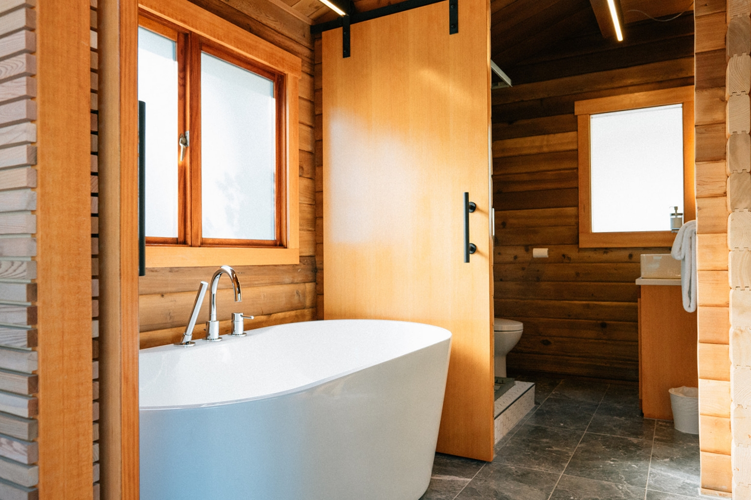 Focal Point - The small but luxurious bathrooms have grey marble heated floors, deep soaker tubs, custom douglas fir vanities with quartz counters and vessel sink, LED backlit arched mirrors, torched cedar pendant lighting, whitewashed cedar slatted walls and fir barn doors.