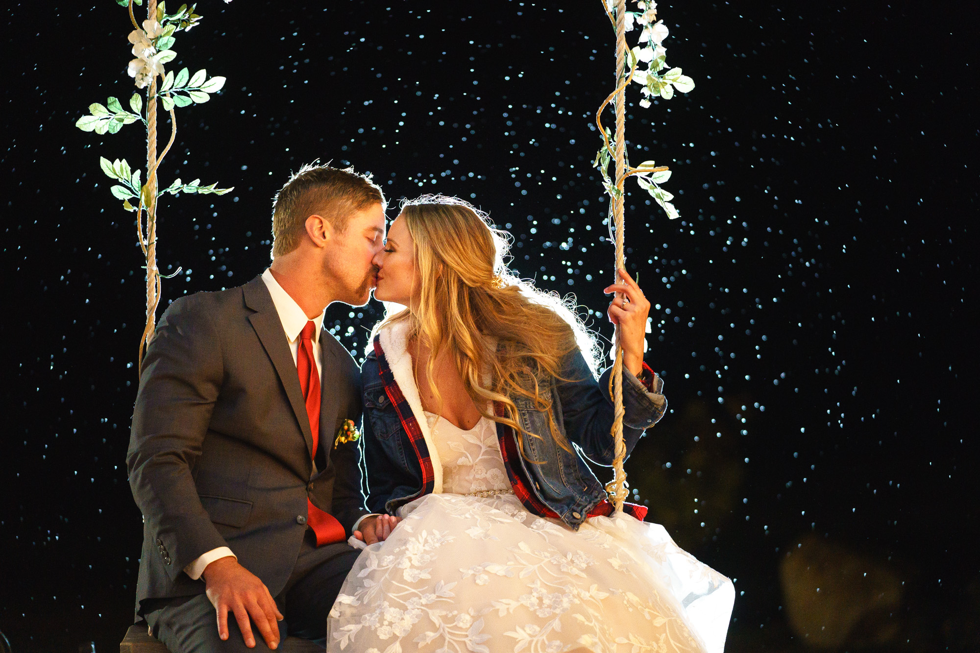 bride and groom in swing with twinkle lights image