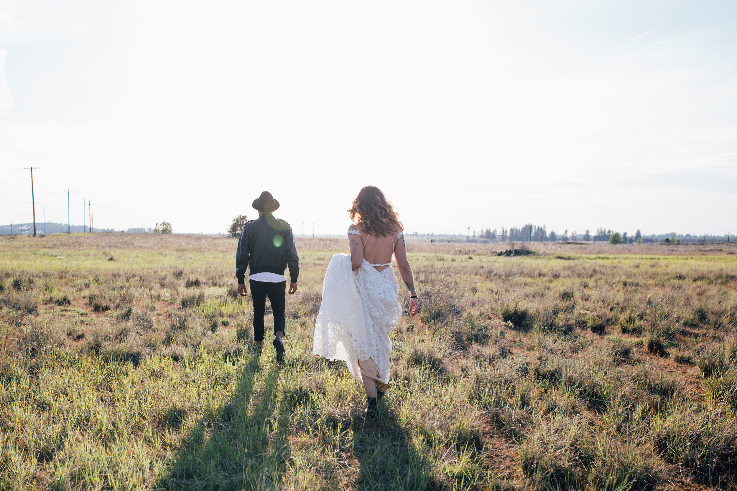 cool elopement spokane wedding walking away bride holding dress