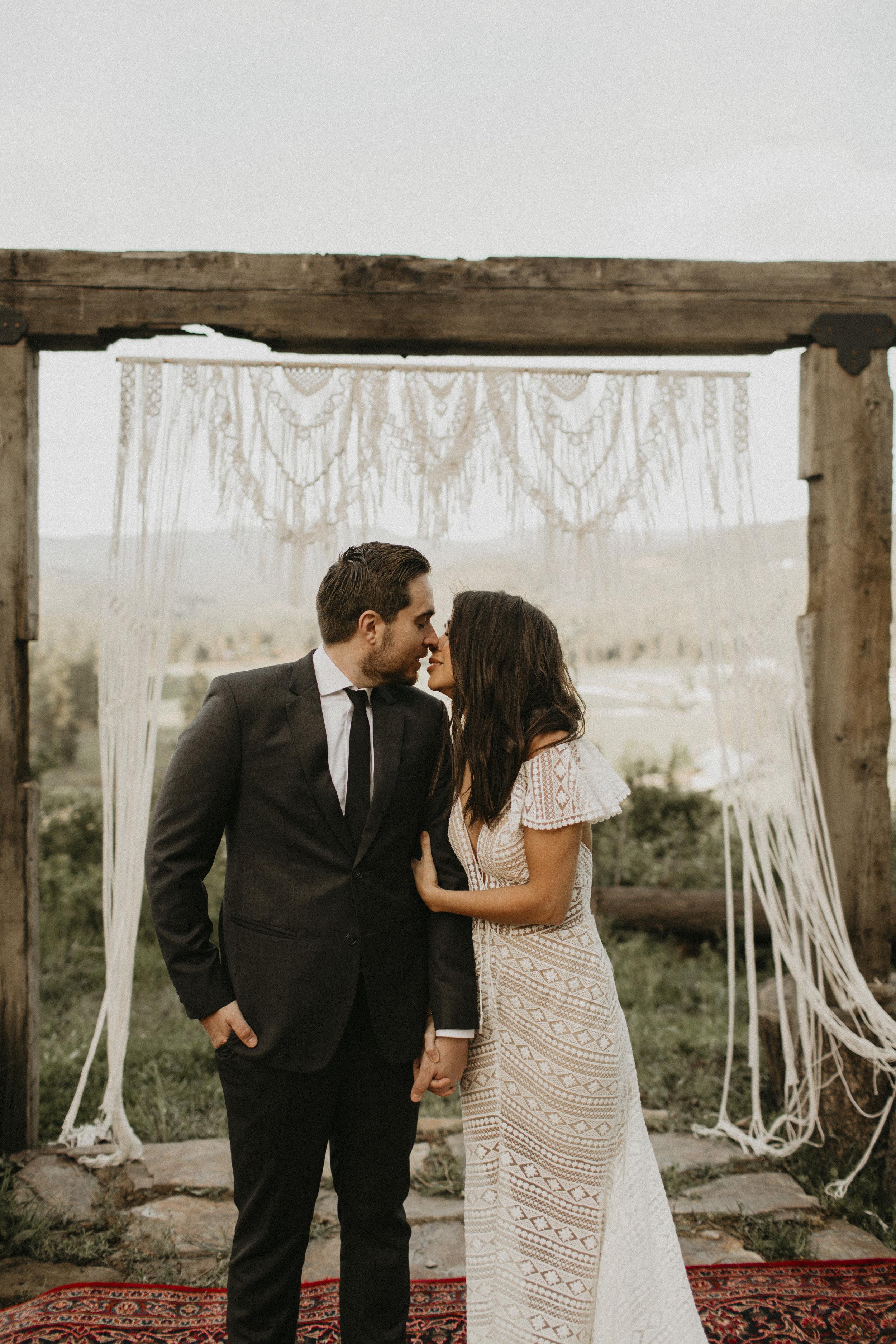 Spokane boho cattle wedding eskimo kiss holding hands wedding ceremony outside