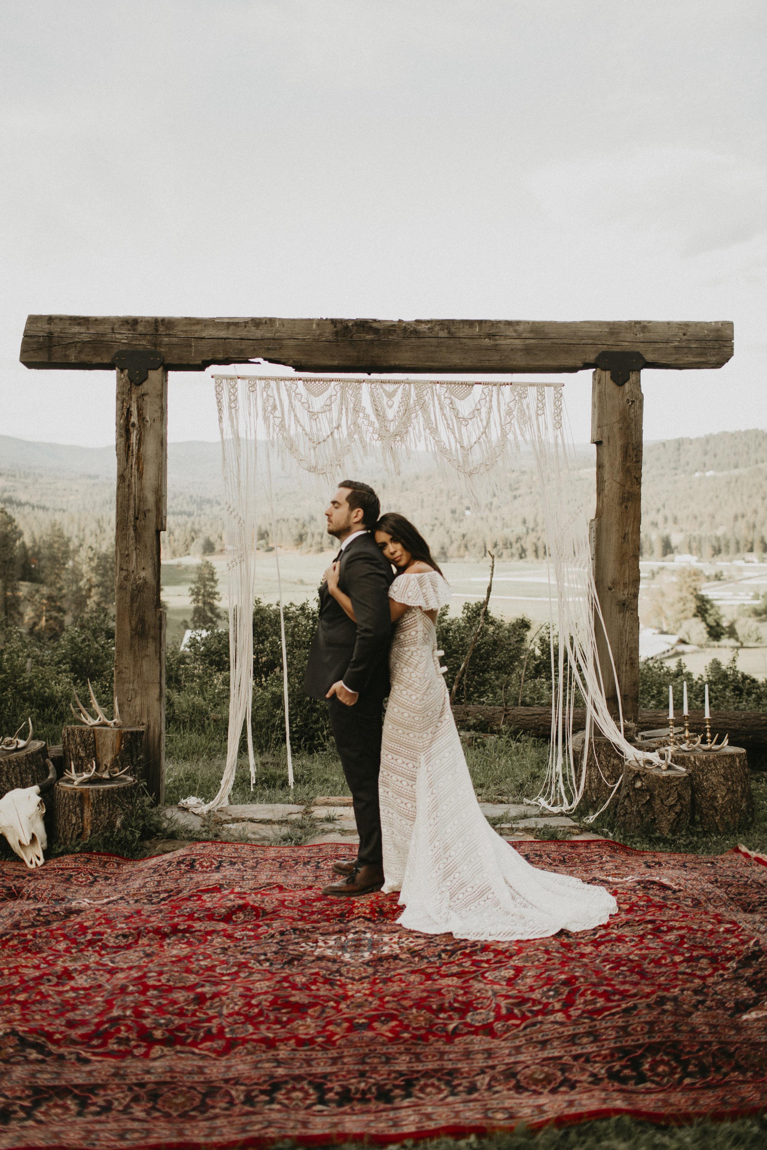 Spokane boho cattle wedding bride hugging groom candles romantic