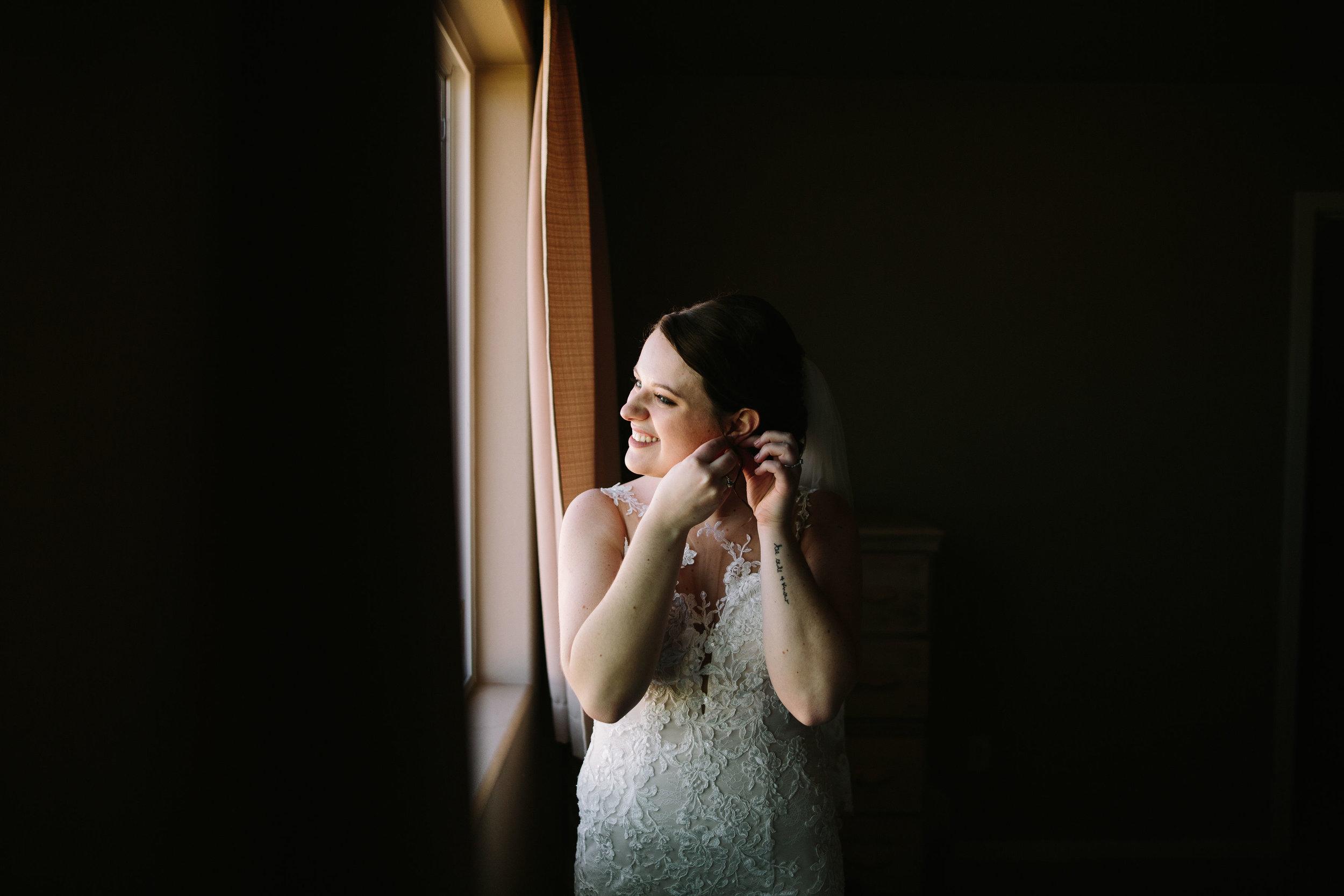 Fun Rustic spokane wedding getting ready earrings smile looking out window
