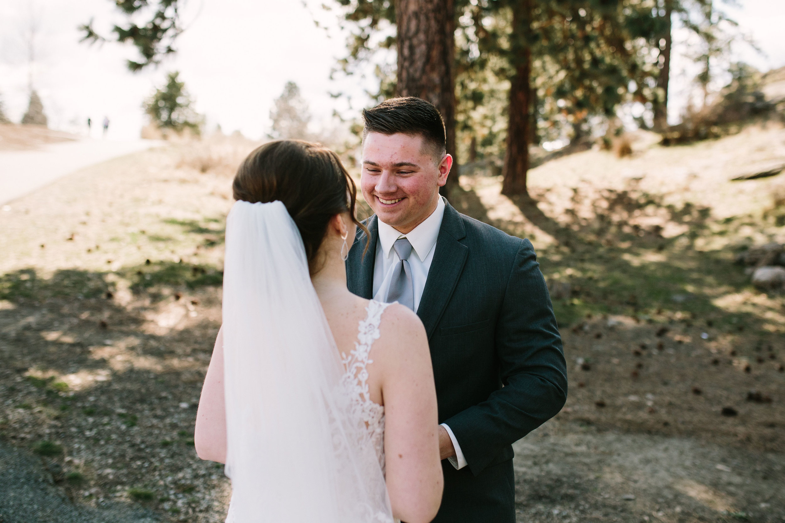 Fun Rustic spokane wedding bride and groom holding hands smiling at each other