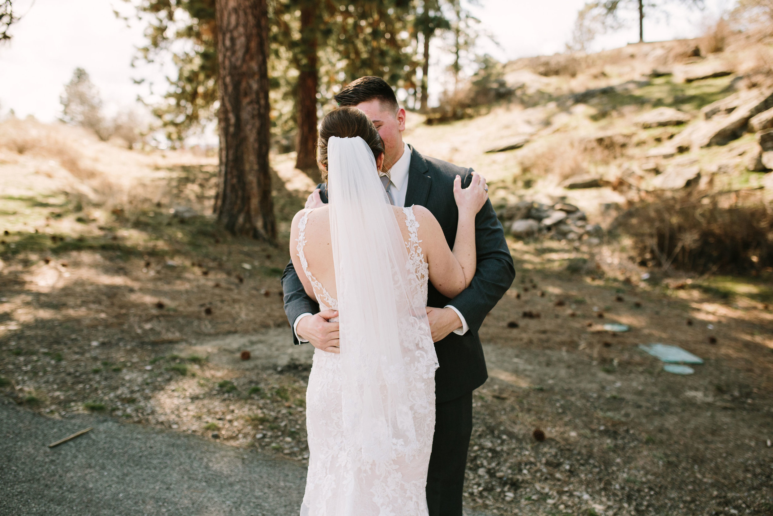 Fun Rustic spokane wedding kissing after first look in love on wedding day