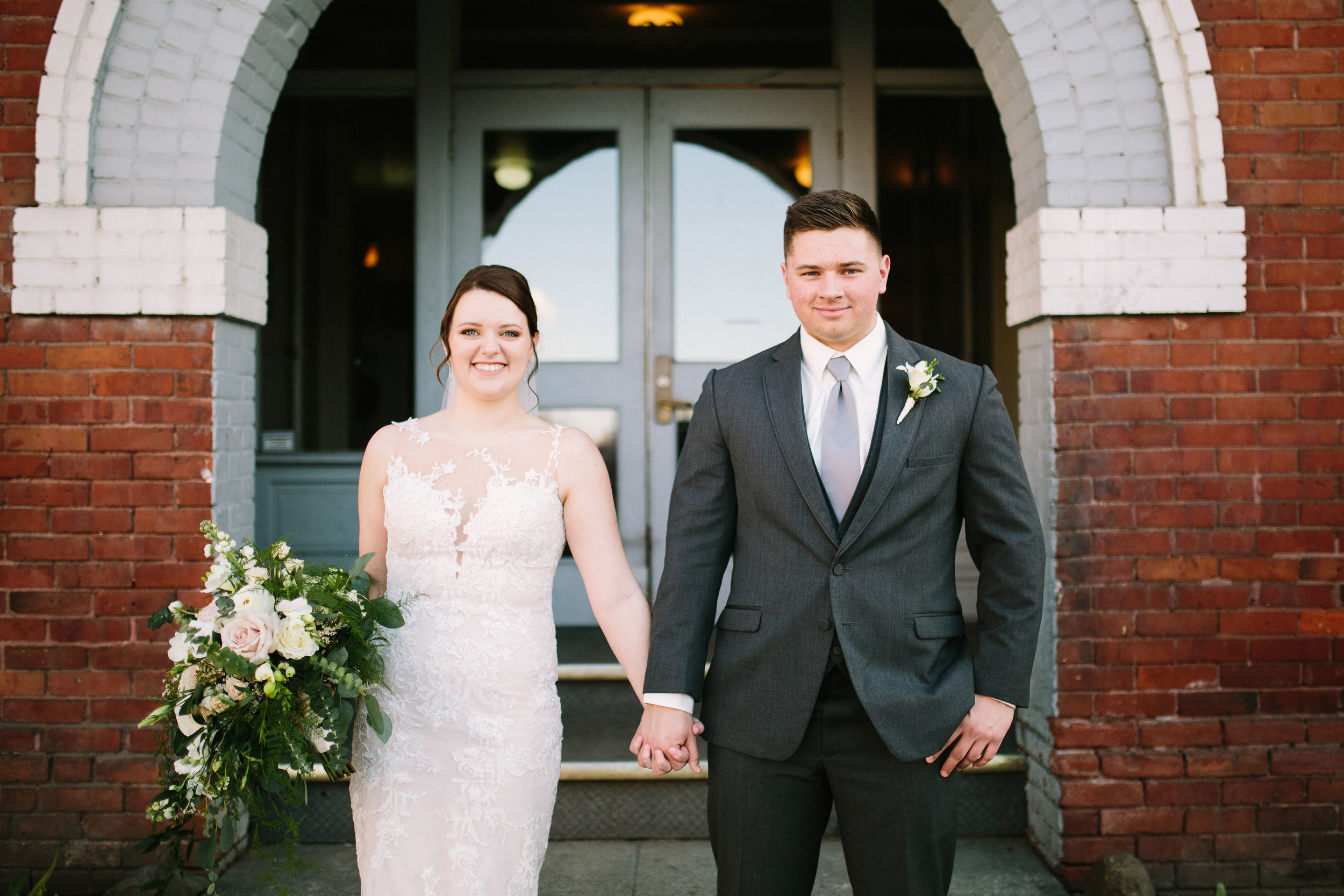 Fun Rustic spokane wedding holding hands with bouquet