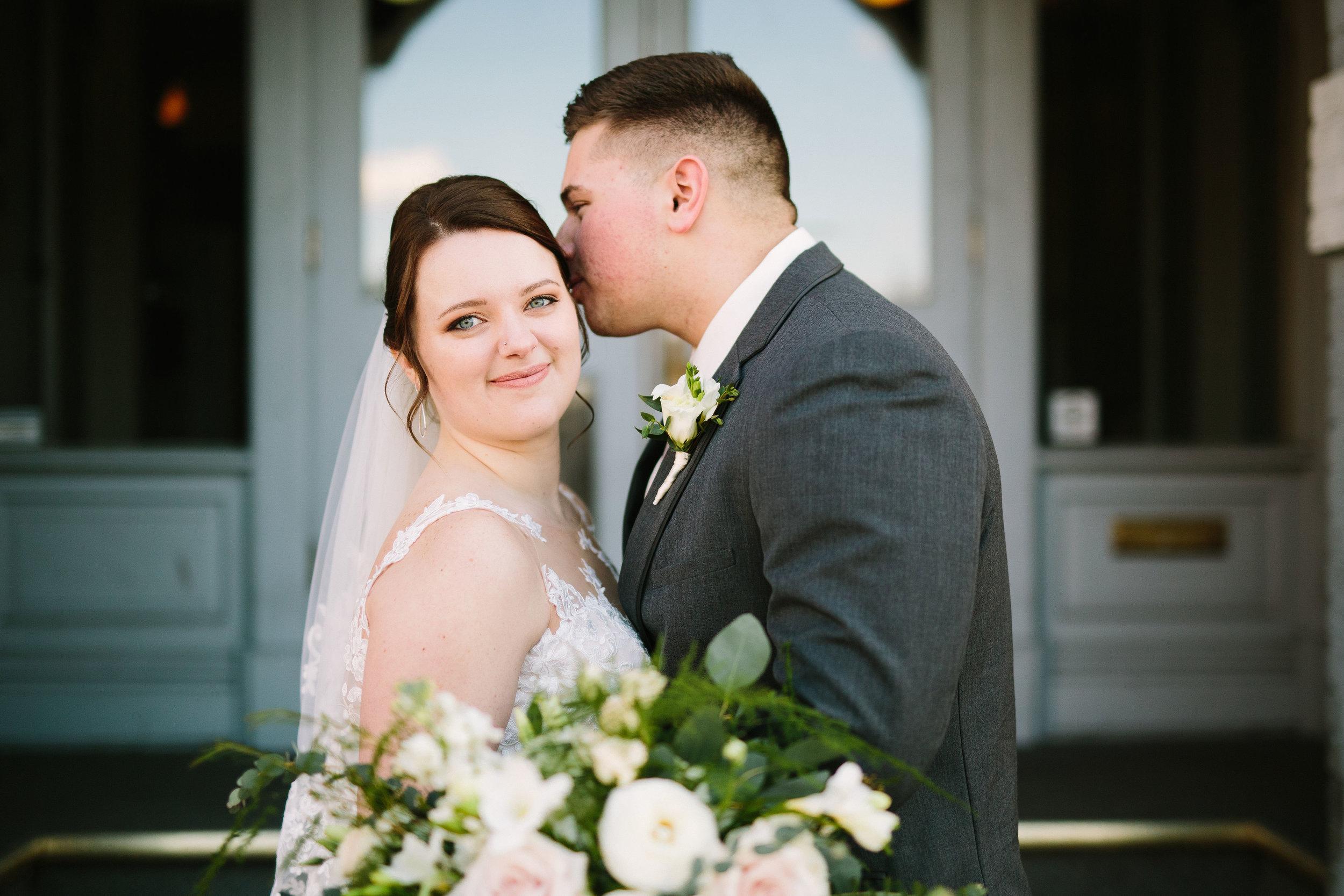 Fun Rustic spokane wedding groom kissing bride on cheek before wedding