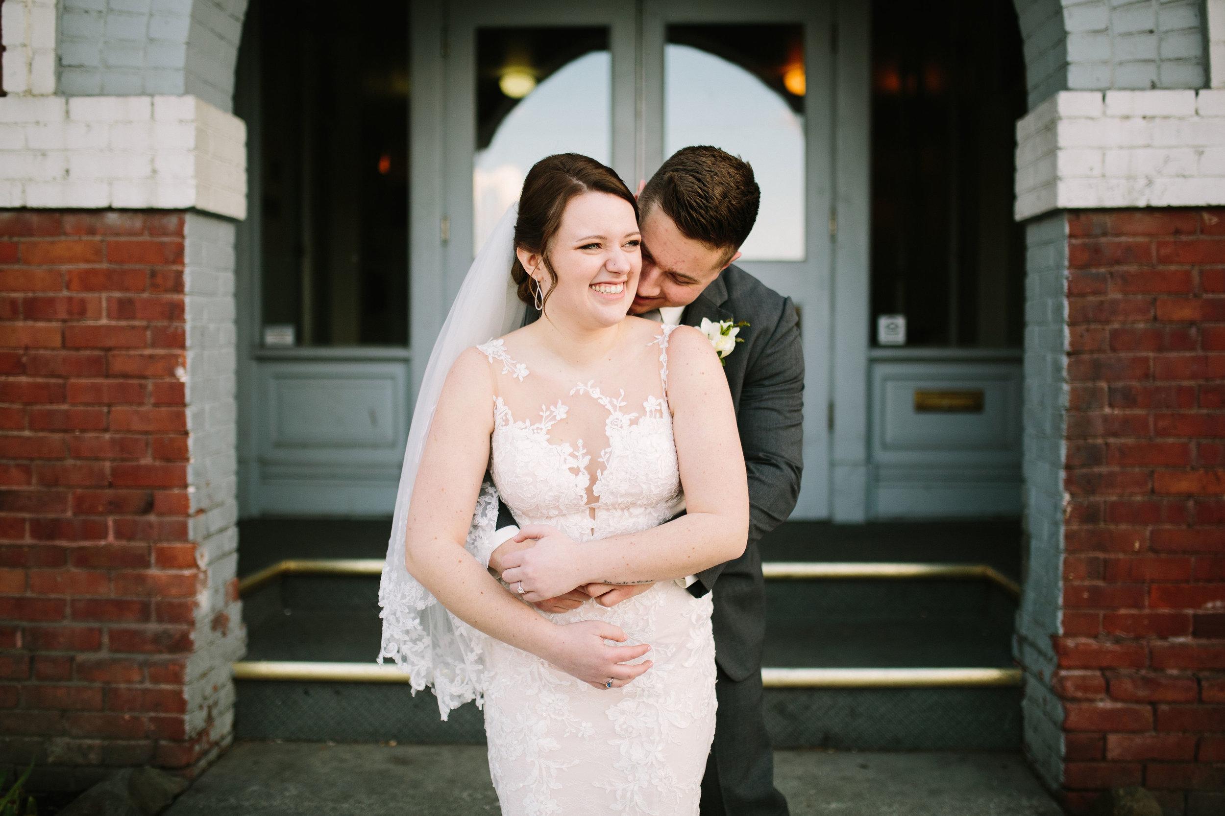 Fun Rustic spokane wedding groom hugging bride from behind cute