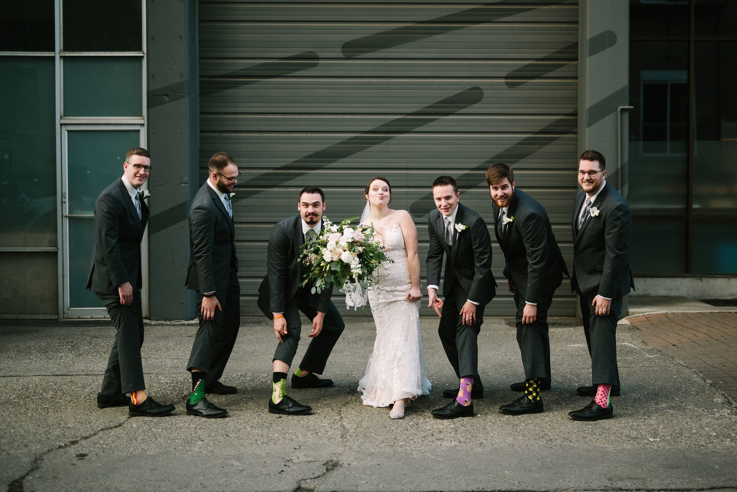Fun Rustic spokane wedding bride and groomsmen showing off shoes and socks together