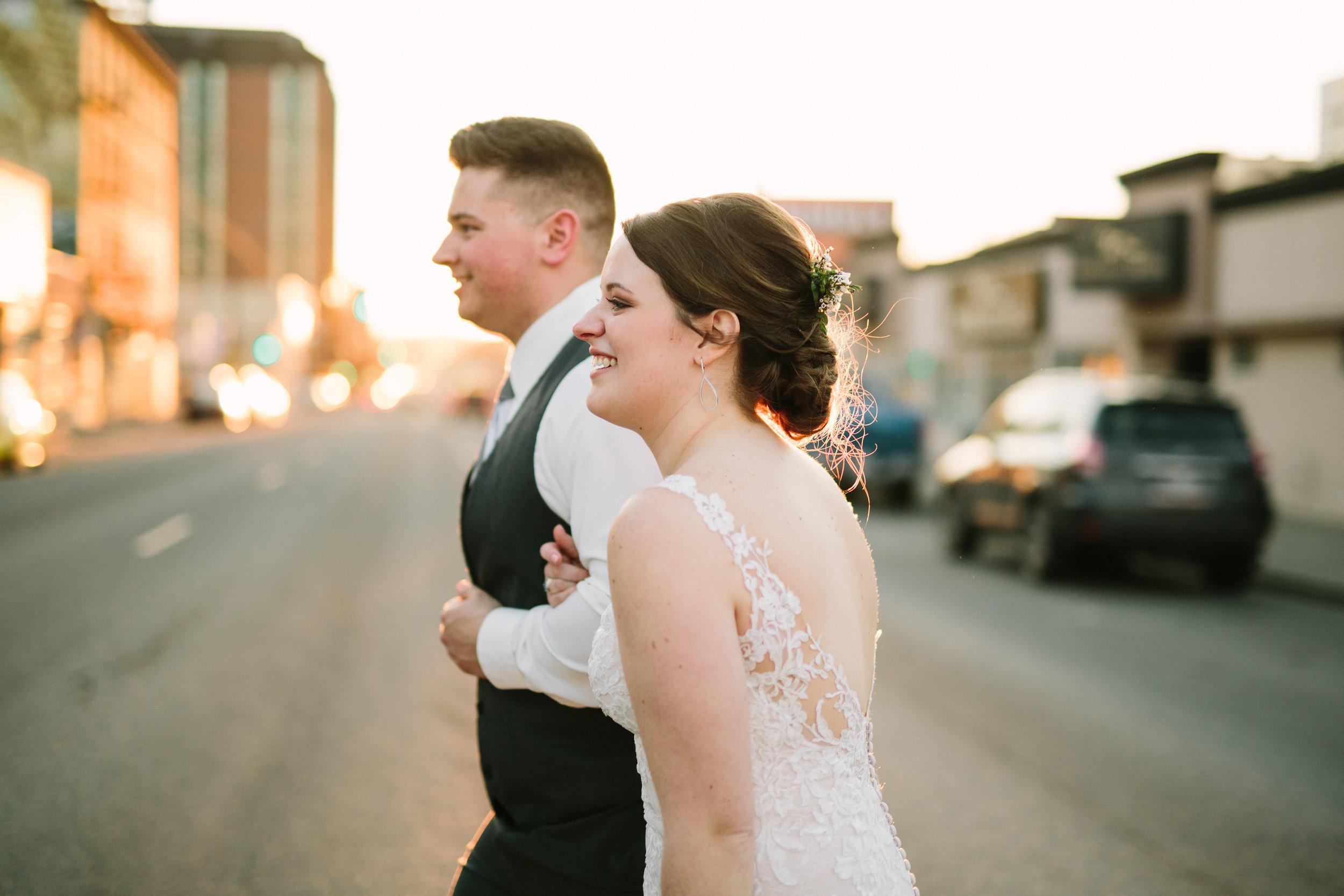 Fun Rustic spokane wedding groom bride walking outside holding hands sunset street