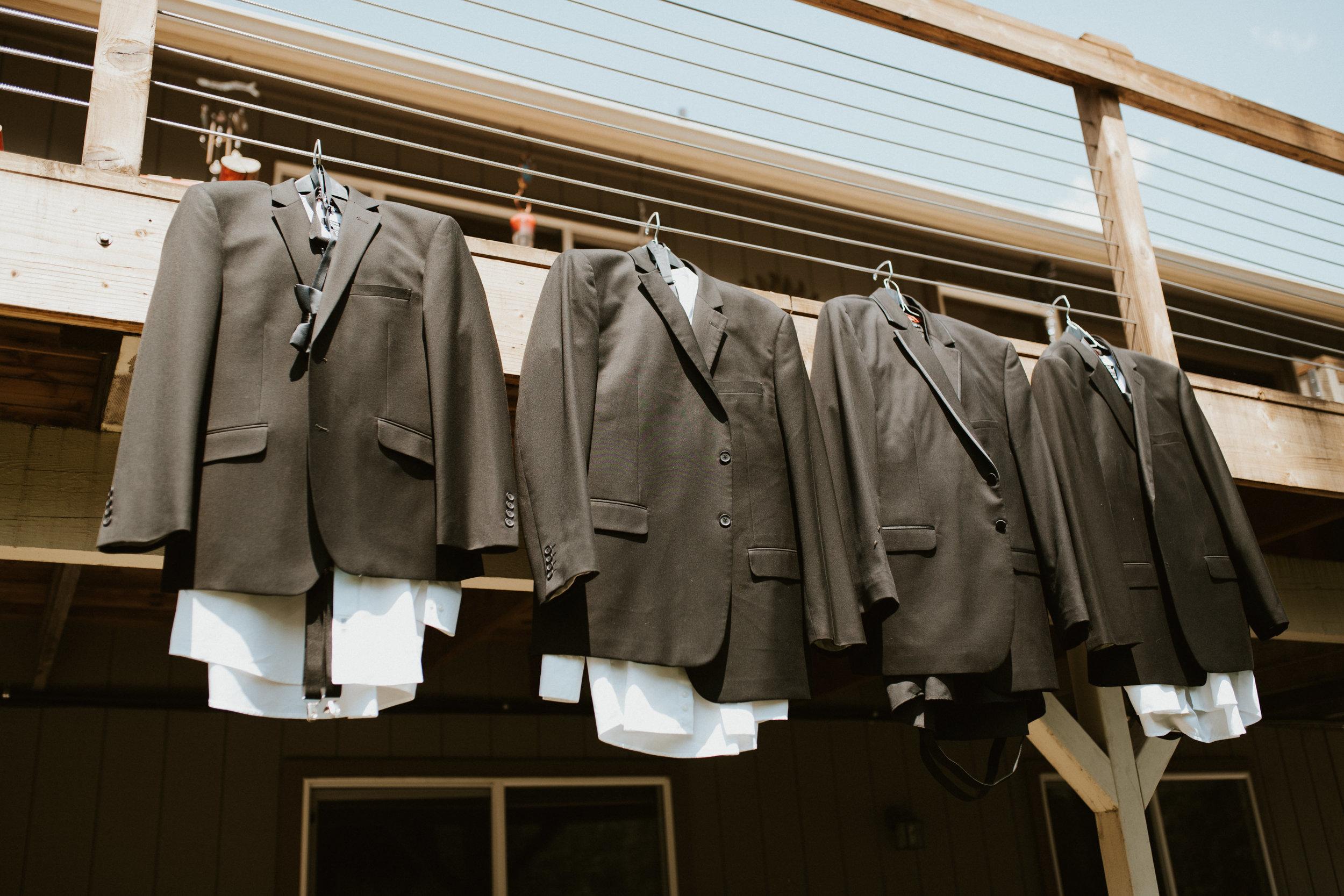 groomsmen tuxes hanging spokane wedding