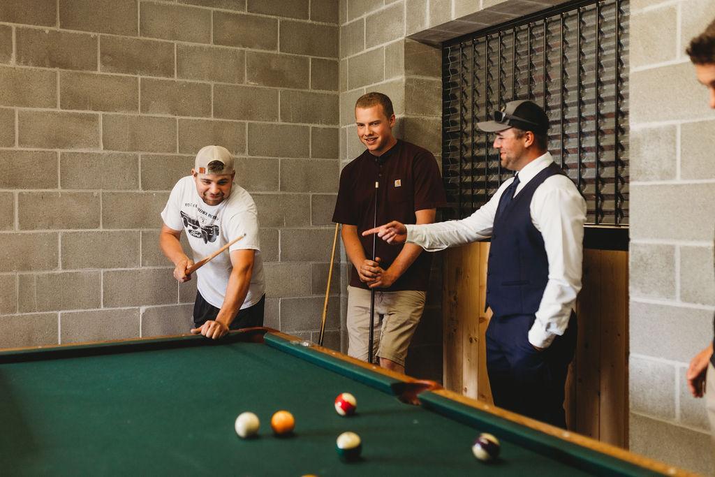 groomsmen getting ready playing pool spokane wedding