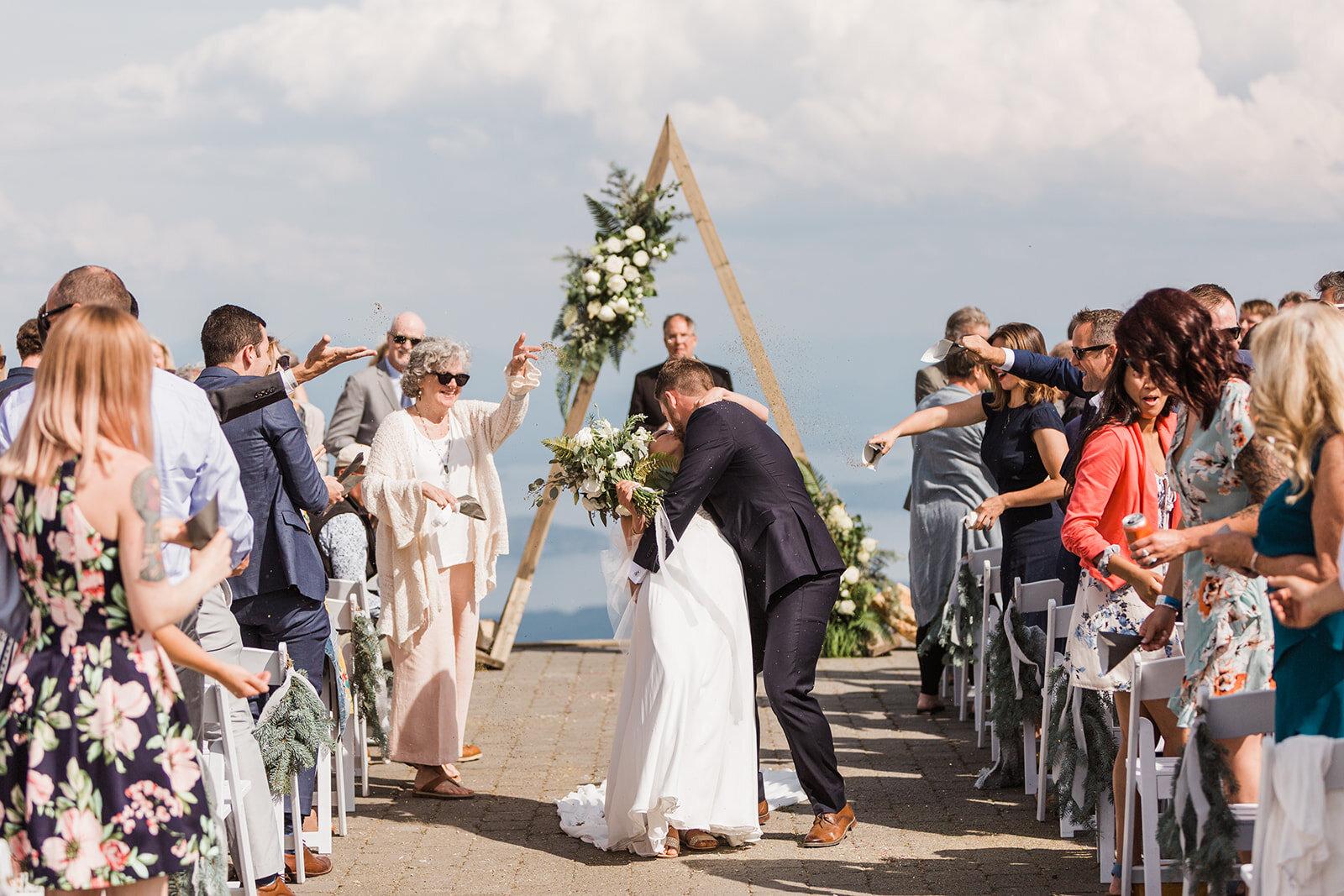 bride and groom down the aisle spokane weddin gkiss