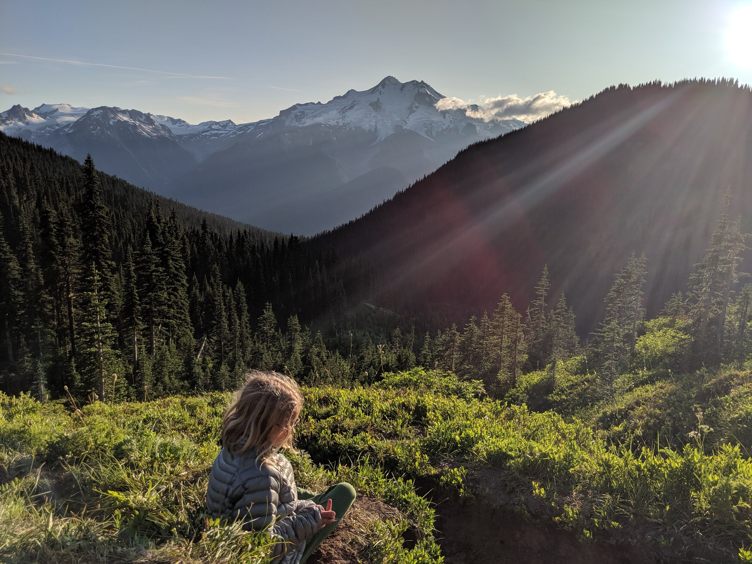 Glacier Peak at sunset. Though Rowan appears to be giving me the finger, she is whittling a stick with her Swiss Army knife.