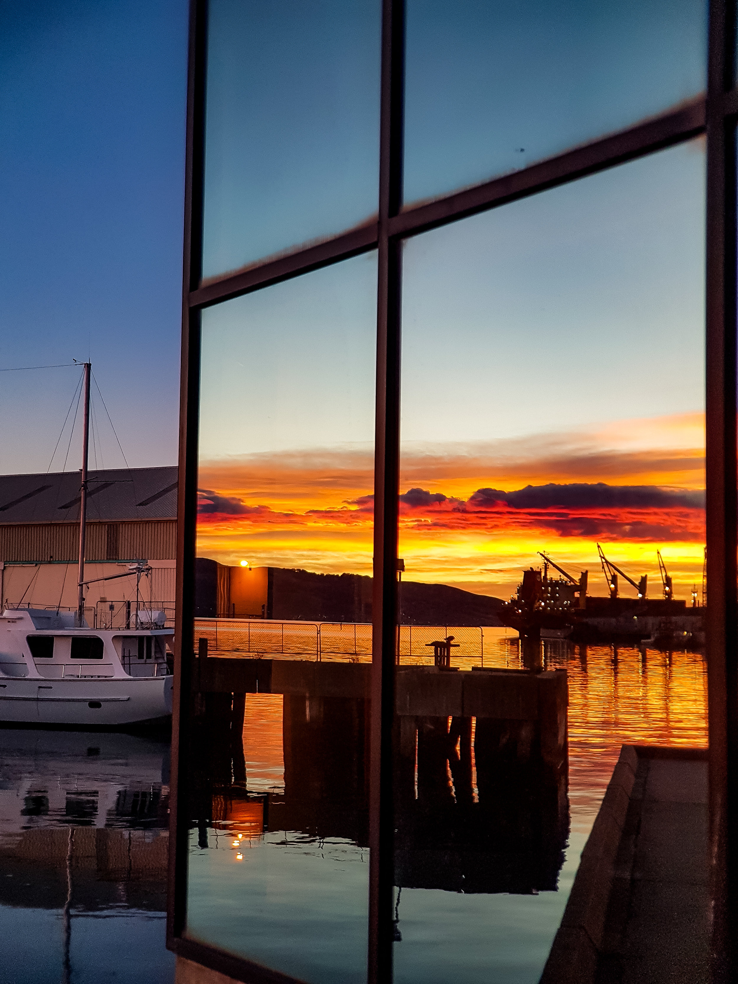 Boat at sunrise reflecting in the Jade building Dunedin