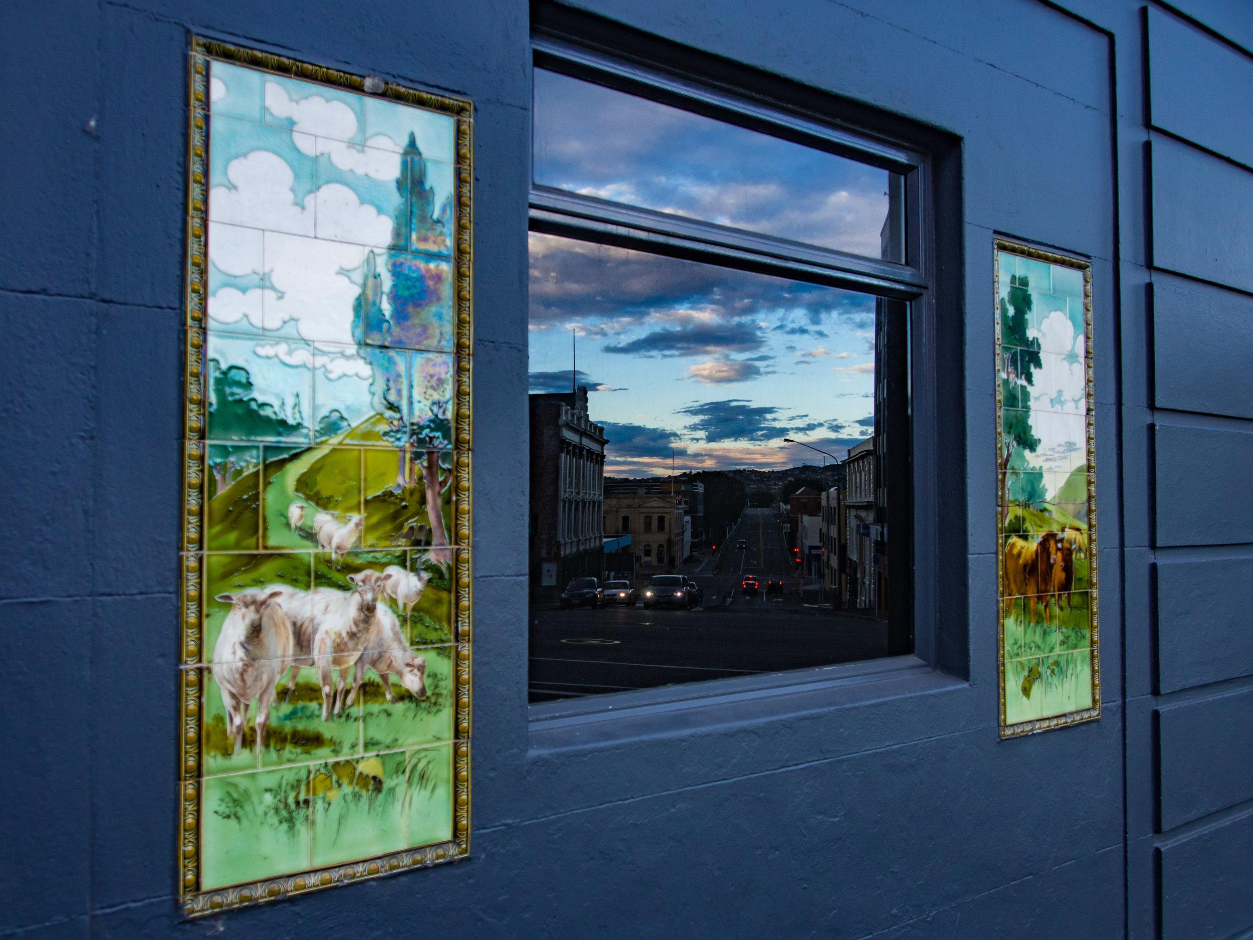 Dunedin shops reflected in a window