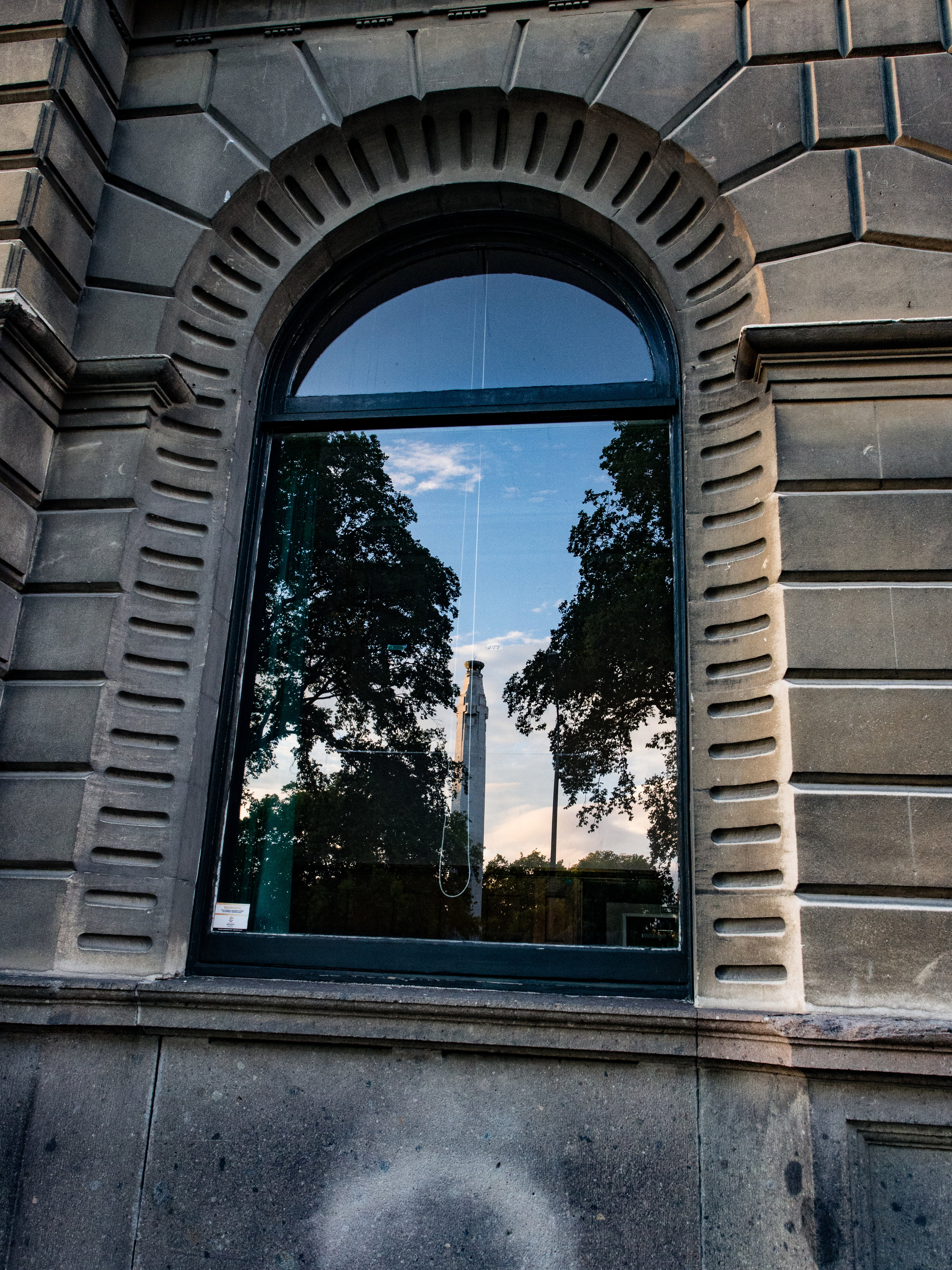 Cenotaph in Dunedin reflected in arched window