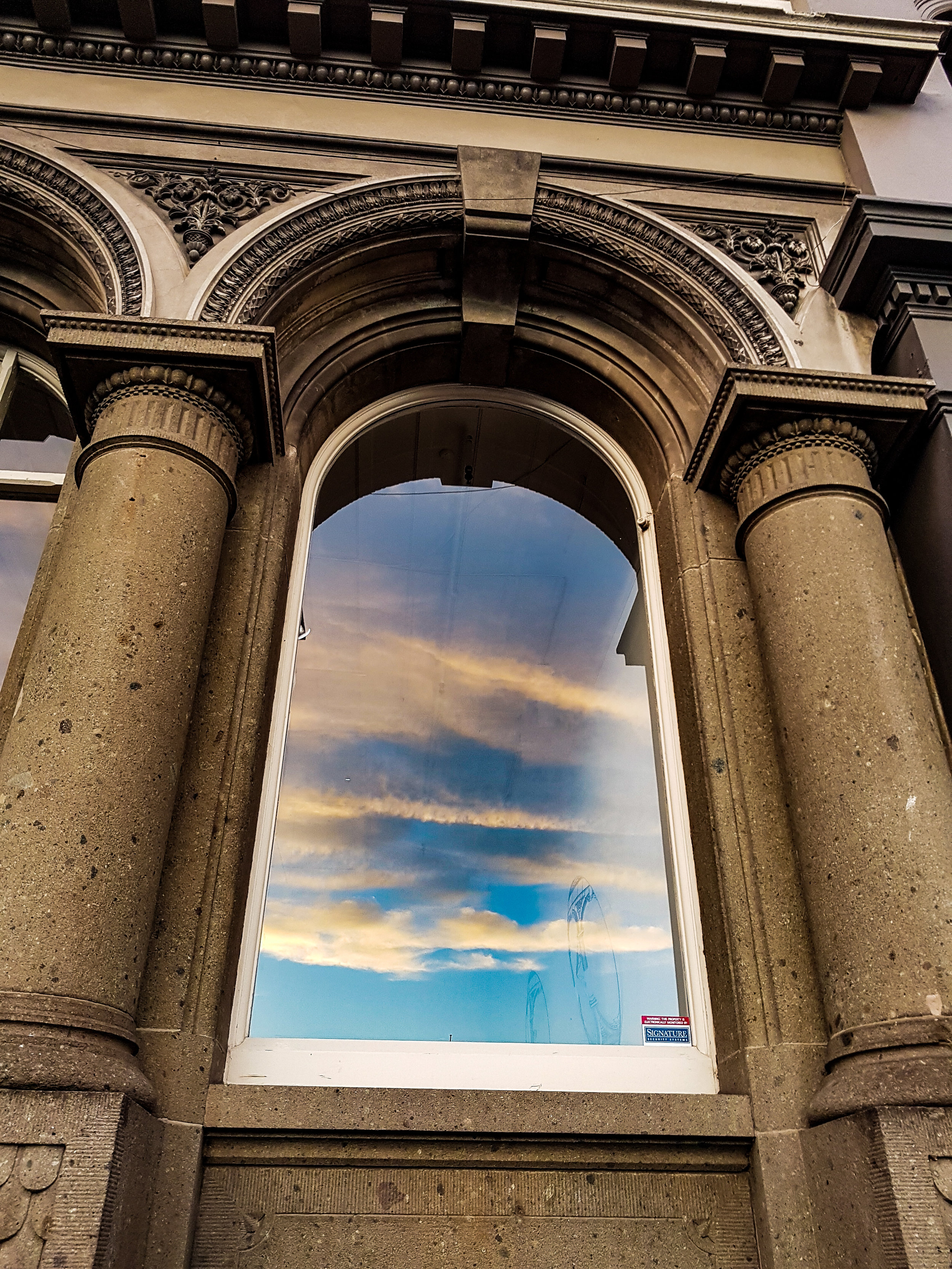 Blue skies in an arched heritage window Dunedin