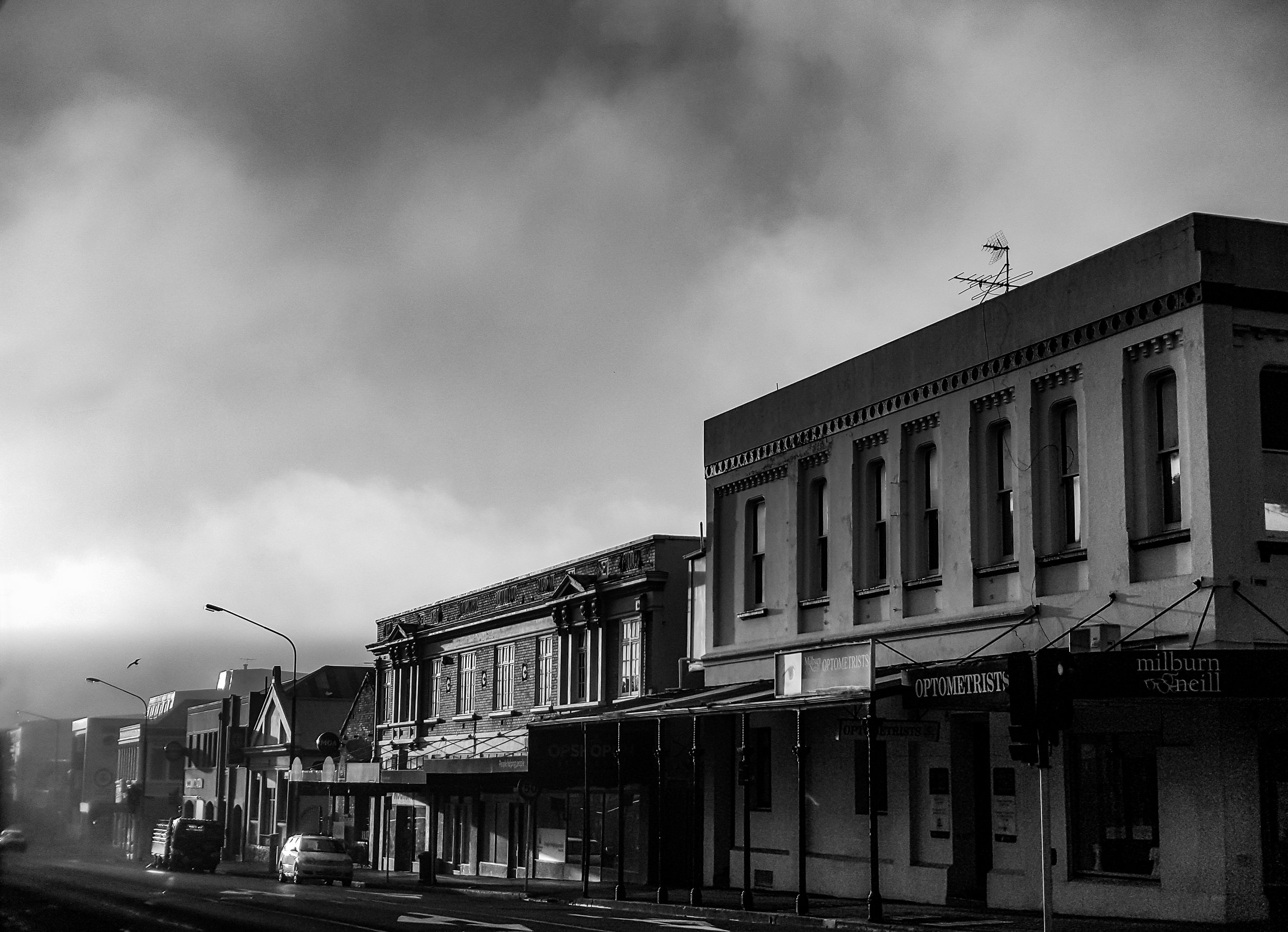 misty clouds over heritage buildings in dunedin black and white