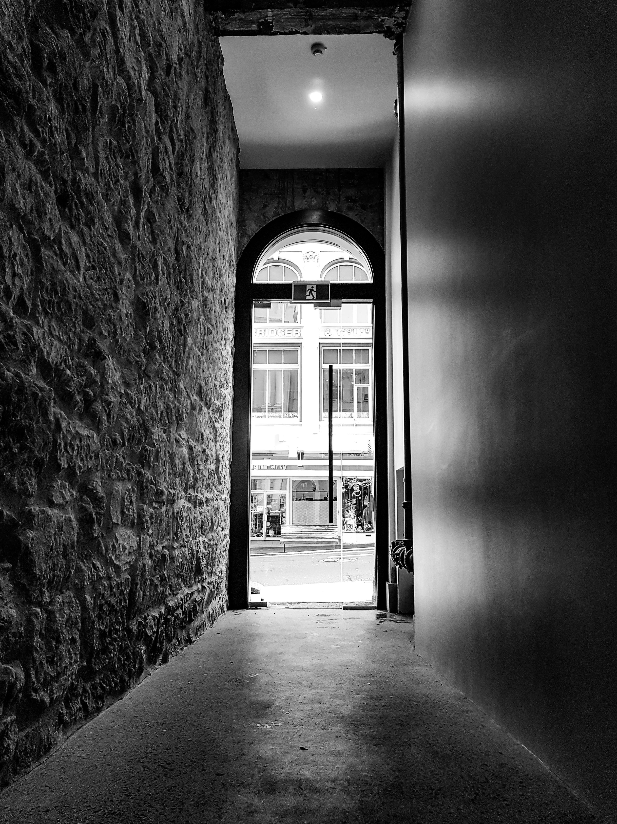 Archway to the street in Dunedin black and white
