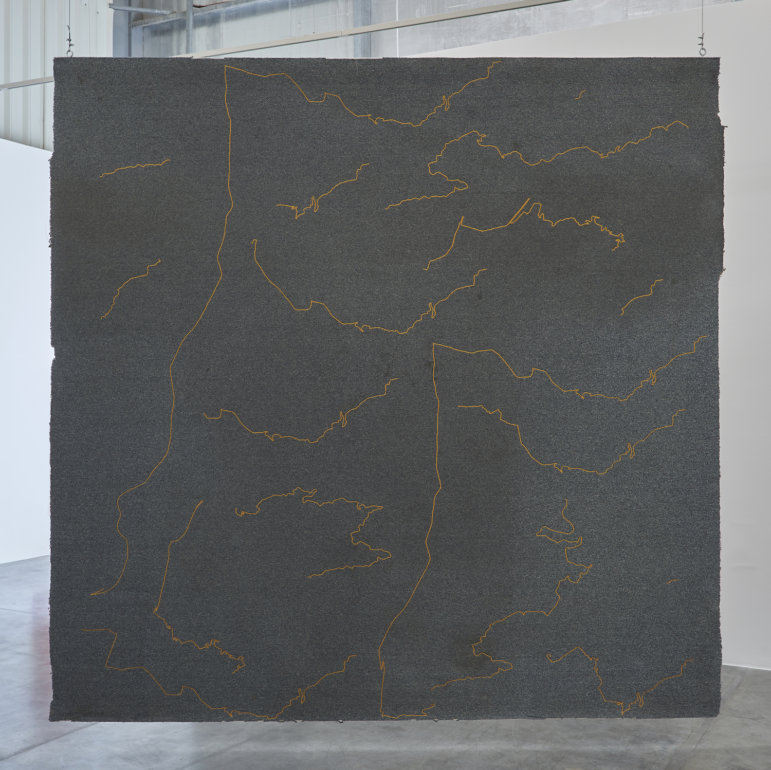 The Encounter of the First and Last Particles of Dust 2019 Used carpet, gold thread embroidery 333.5 x 336.5 cm  The carpet of the room which the artist occupied as a teenager, from 1995 to 2001, is torn off and embroidered with the 18 most significant trajectories underwent during this time span.