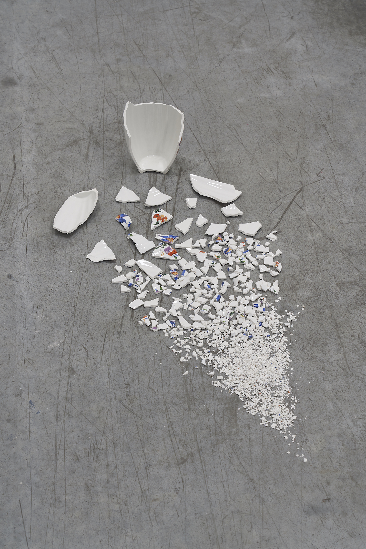 Accelerated Time 2014 Vase broken in fragments size of installation: 50cm long  A vase is broken into smaller and smaller fragments, until some of its fragments are reduced     to powder.